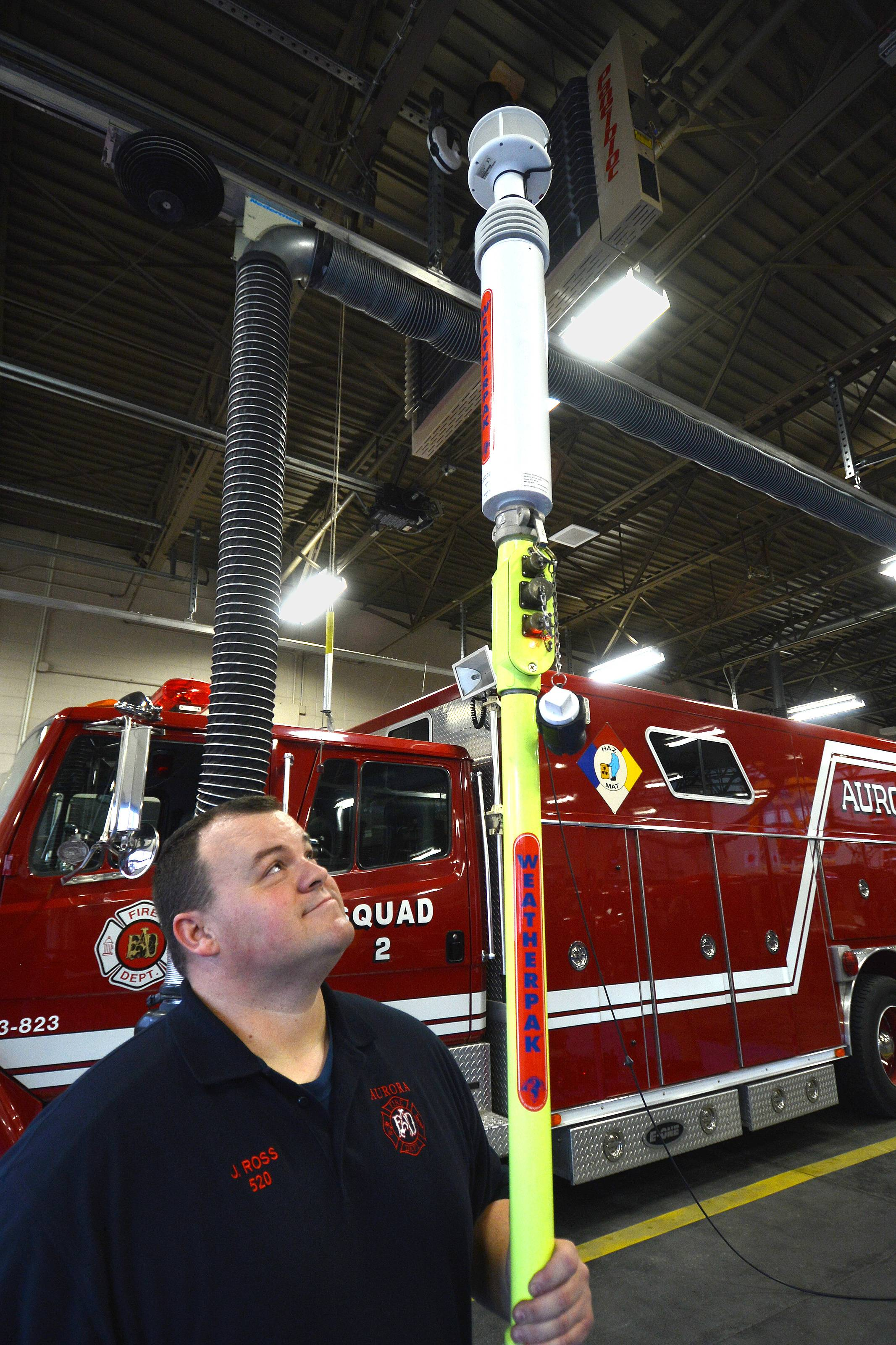 Aurora Fire Department hazmat specialist John Ross looks at a portable weather station that monitors temperature, humidity, wind direction and speed.