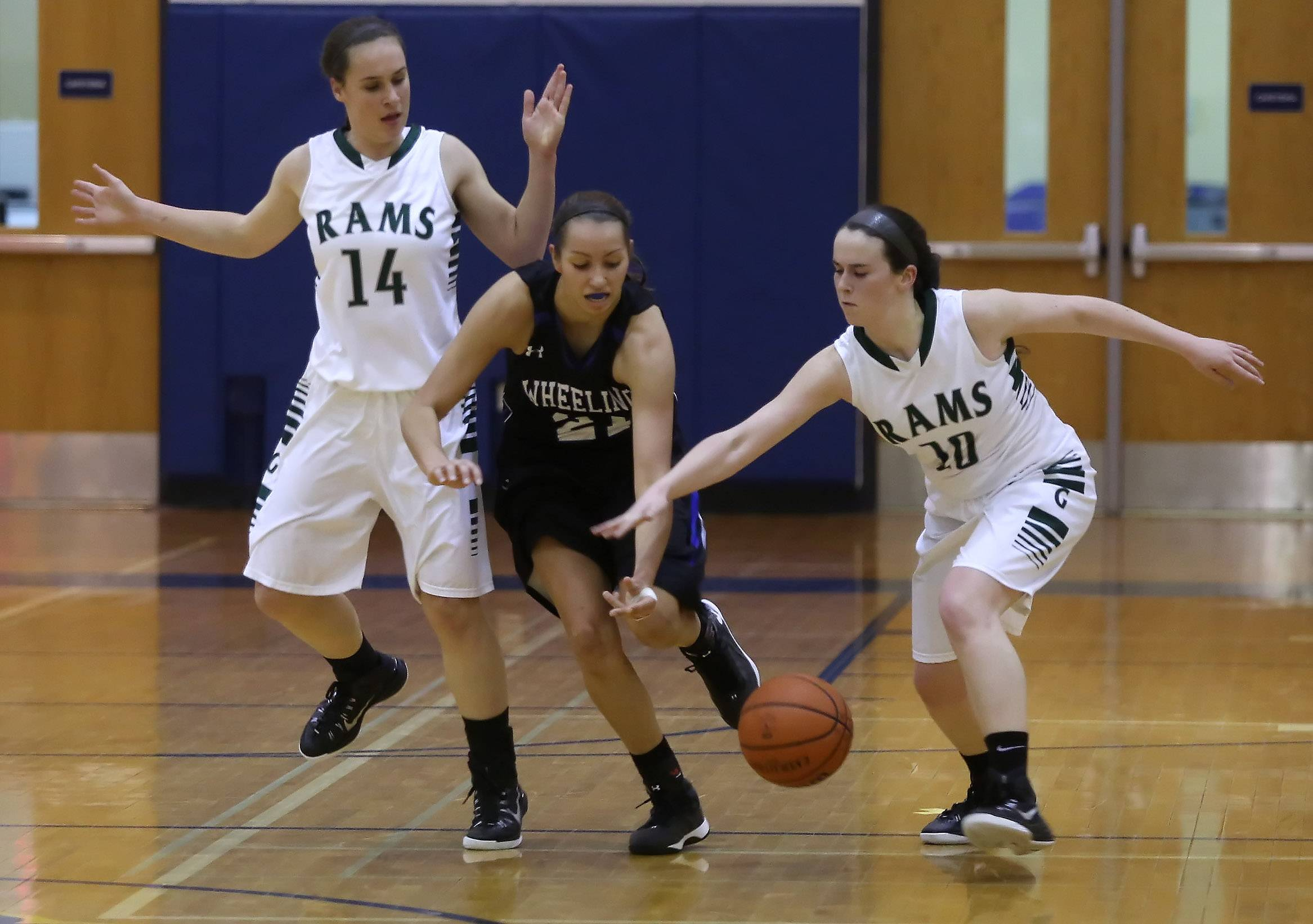 Grayslake Central players Kelly Moroney, right, and Kayley Larson battle Wheeling player Deanna Kuzmanic for a loose ball.