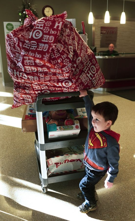 "Dominick Brigham, 3, helps the ""superhero collective"" deliver toys to children at Northwest Community Hospital."