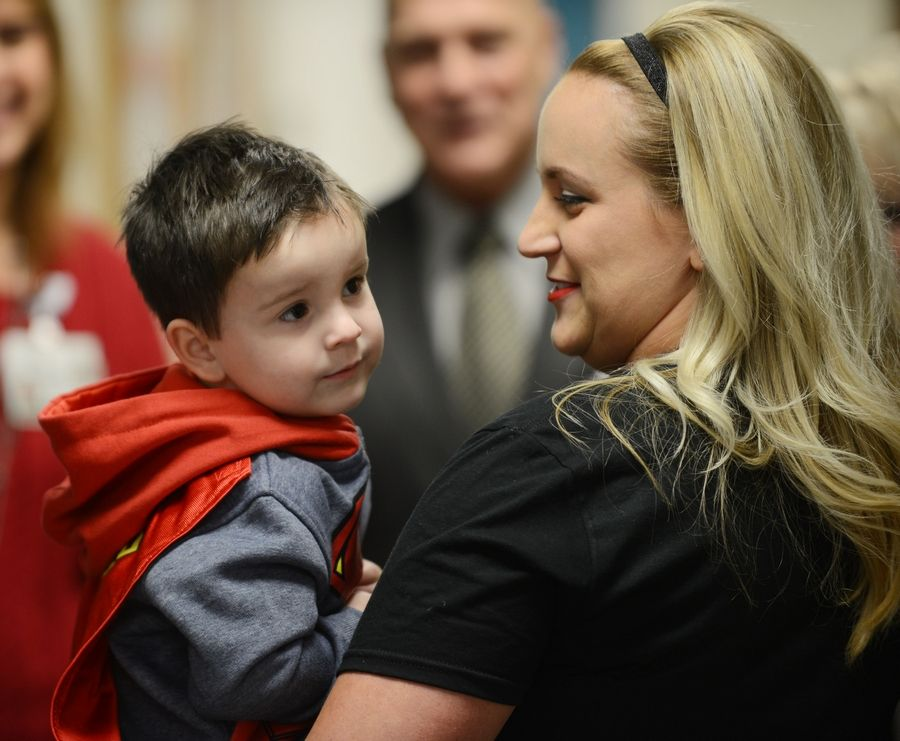 Dominick Brigham, 3, held by his mom, Melissa, helps deliver gifts to children at Northwest Community Hospital Tuesday.