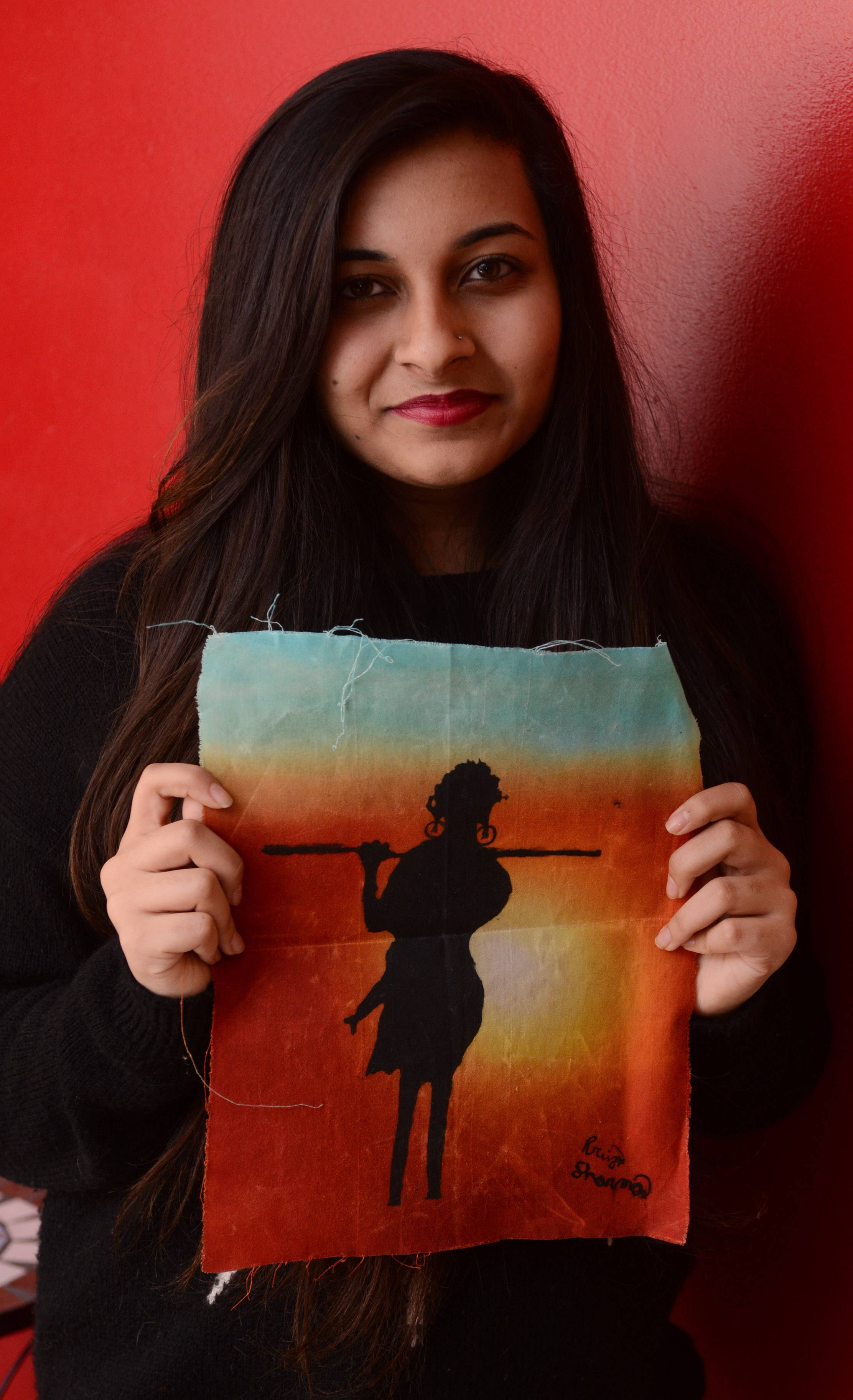 Schaumburg High School junior Priya Sharma spent three weeks in Tanzania over the summer, where she taught math and reading to children in schools and orphanages. She is holding her painting inspired by her experiences in Tanzania.