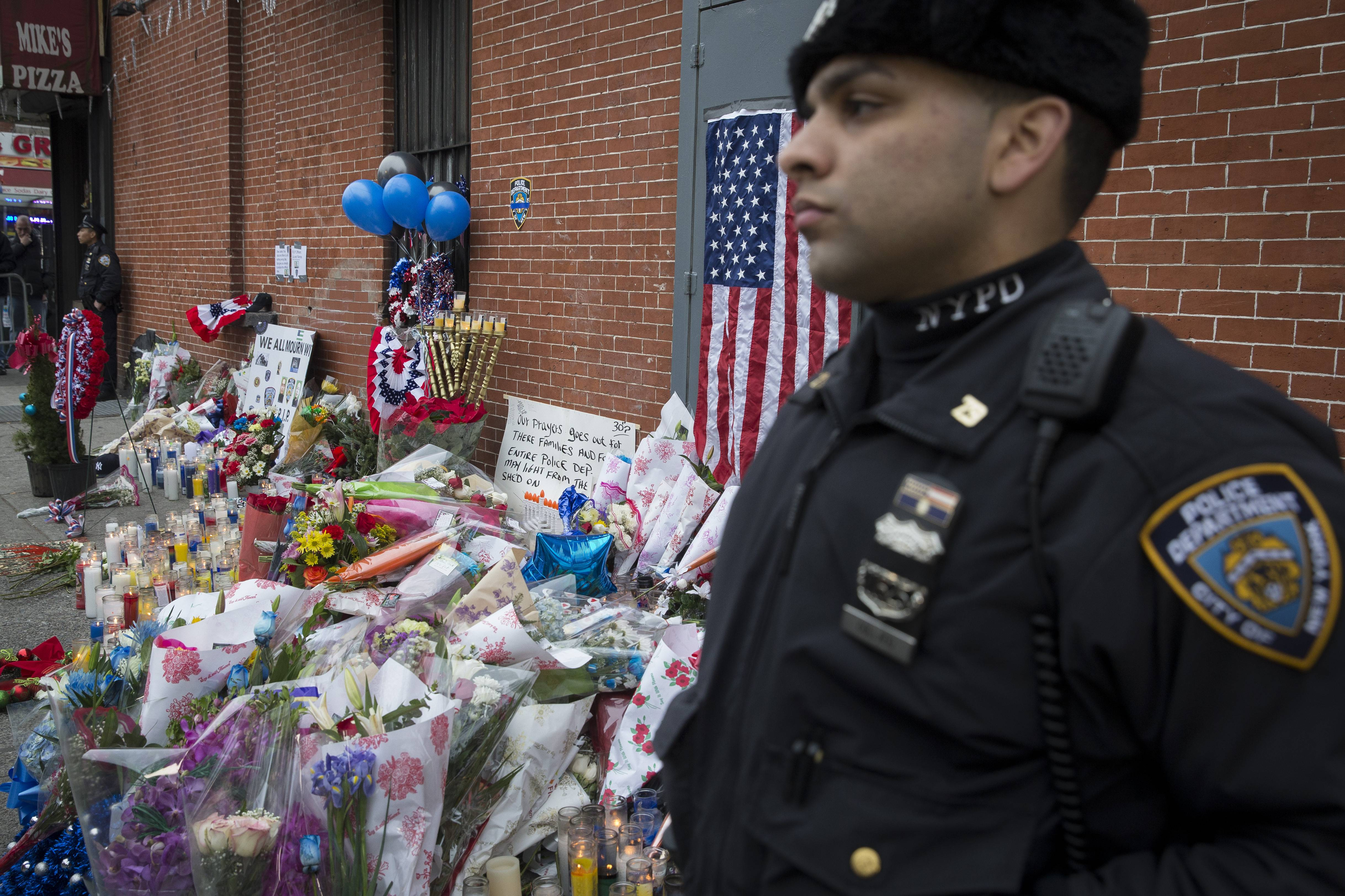 A New York Police Department officer stands guard beside a makeshift memorial Monday near the site where officers Rafael Ramos and Wenjian Liu were murdered in the Brooklyn borough of New York. Seven people have been charged with making threats against New York police officers in the days since the slayings of the two officers.