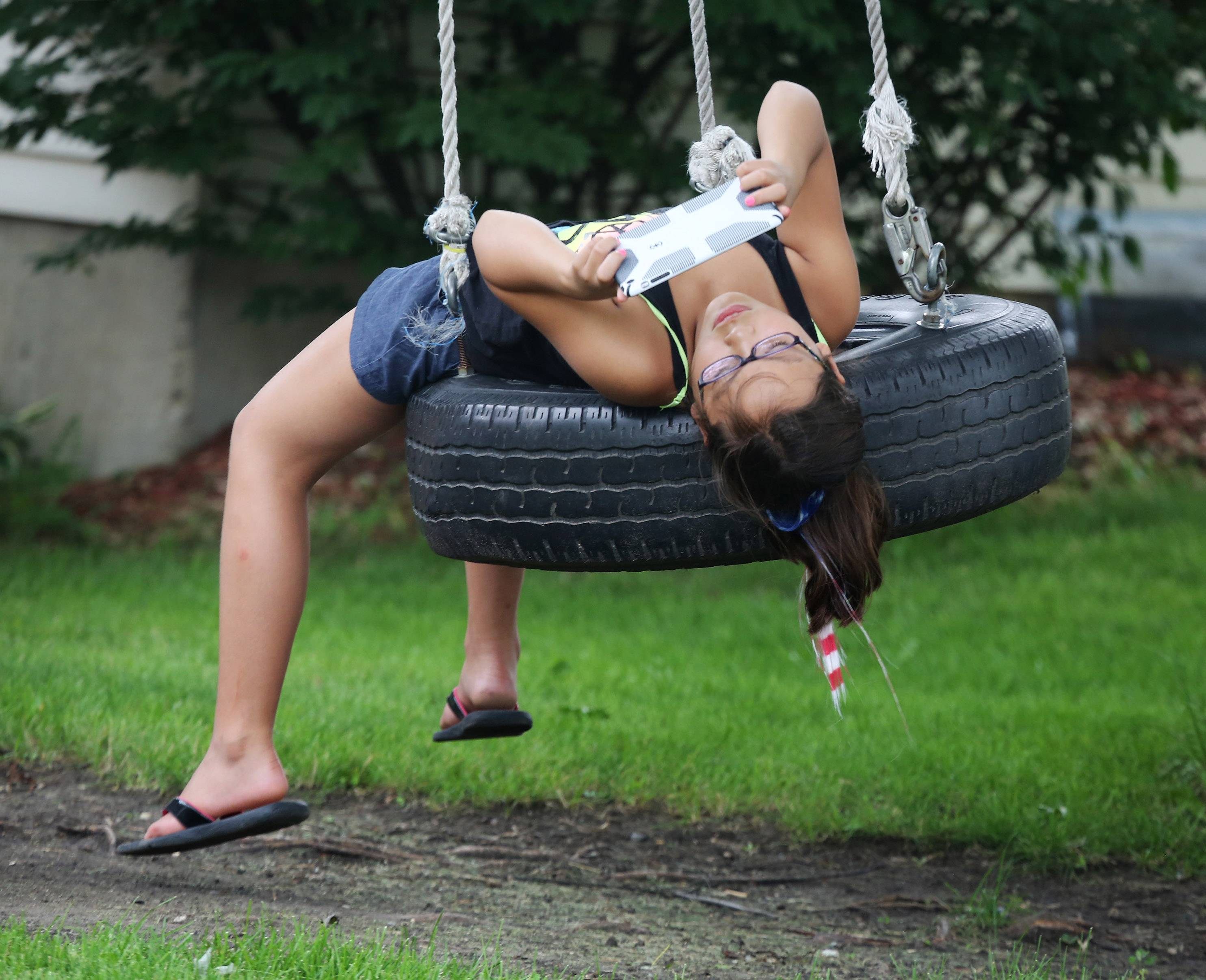 Andrea Deleon, 11, of Buffalo Grove, relaxes on a tire swing at her grandparent's Mundelein home as she plays a game on her iPad.