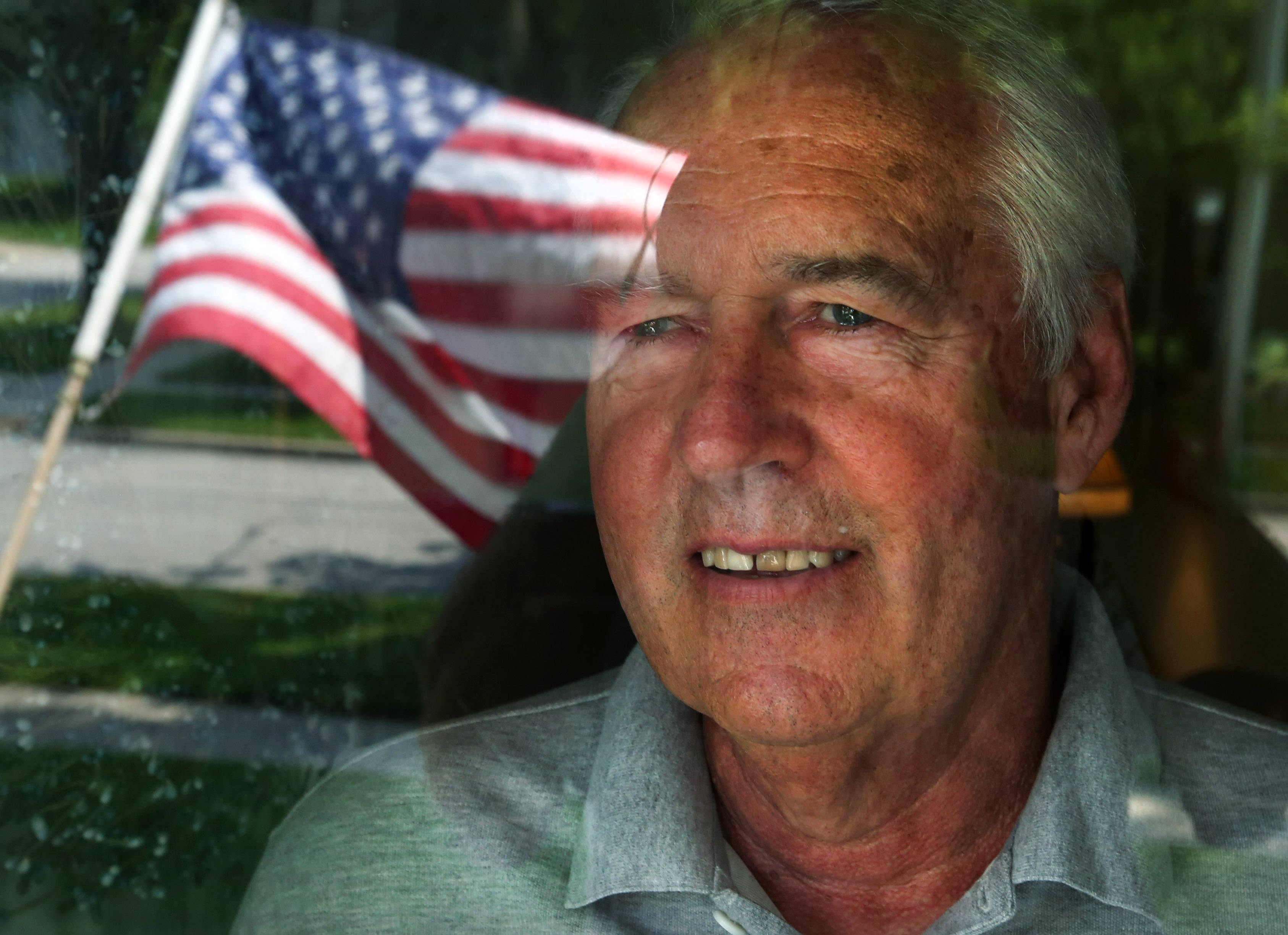 John Malcom looks through his front door window with the reflection of an American flag that is hanging near the front of door of his home in Arlington Heights. Malcom served in the Army National Guard from 1967-1972.