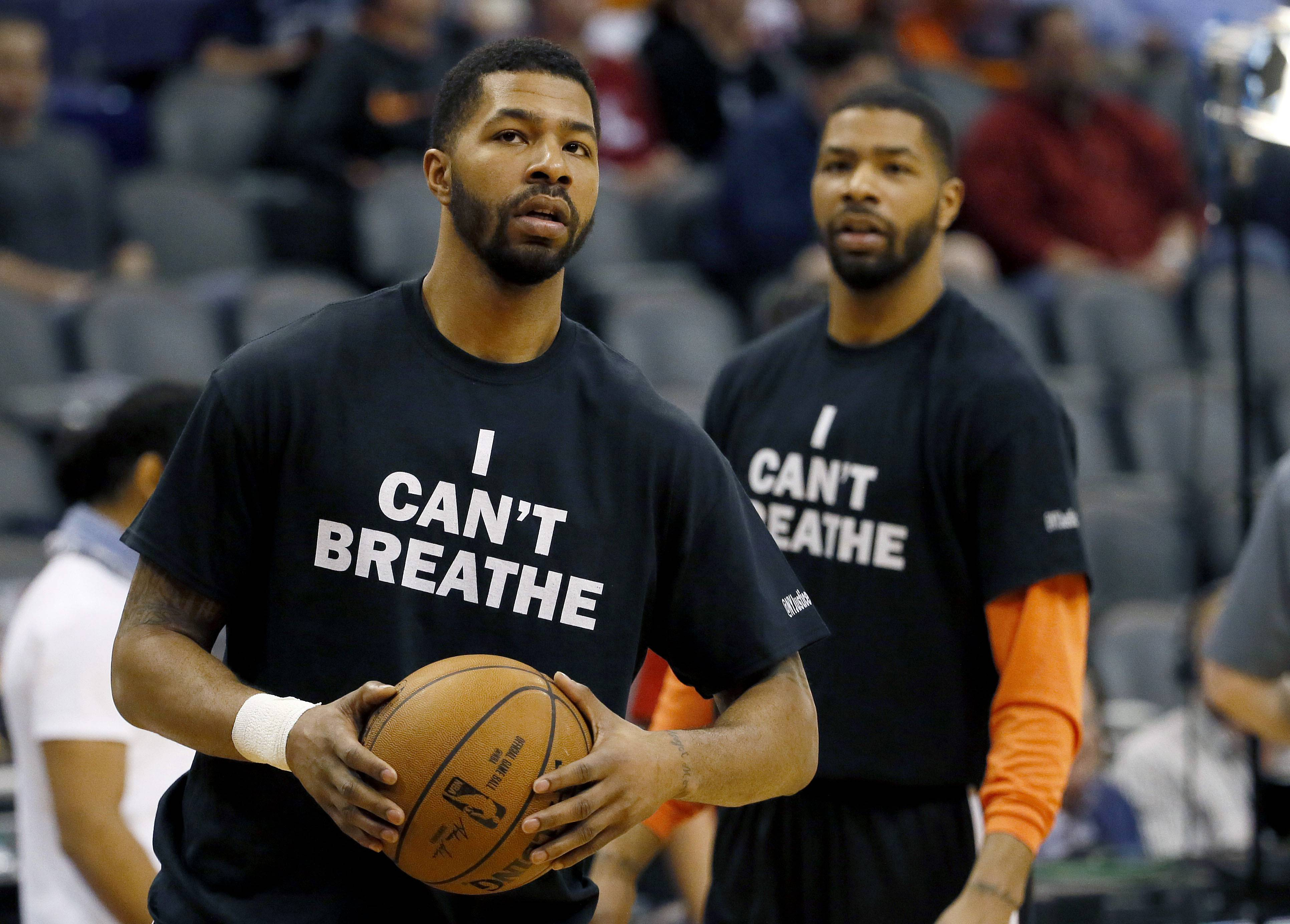 "Phoenix Suns' Markieff Morris, left, and his brother, Marcus Morris, warm up prior to an NBA basketball game against the Milwaukee Bucks, Monday, Dec. 15, 2014, in Phoenix. Several athletes have worn ""I Can't Breathe"" shirts during warm ups in support of the family of Eric Garner, who died July 17 after a police officer placed him in a chokehold when he was being arrested for selling loose, untaxed cigarettes."