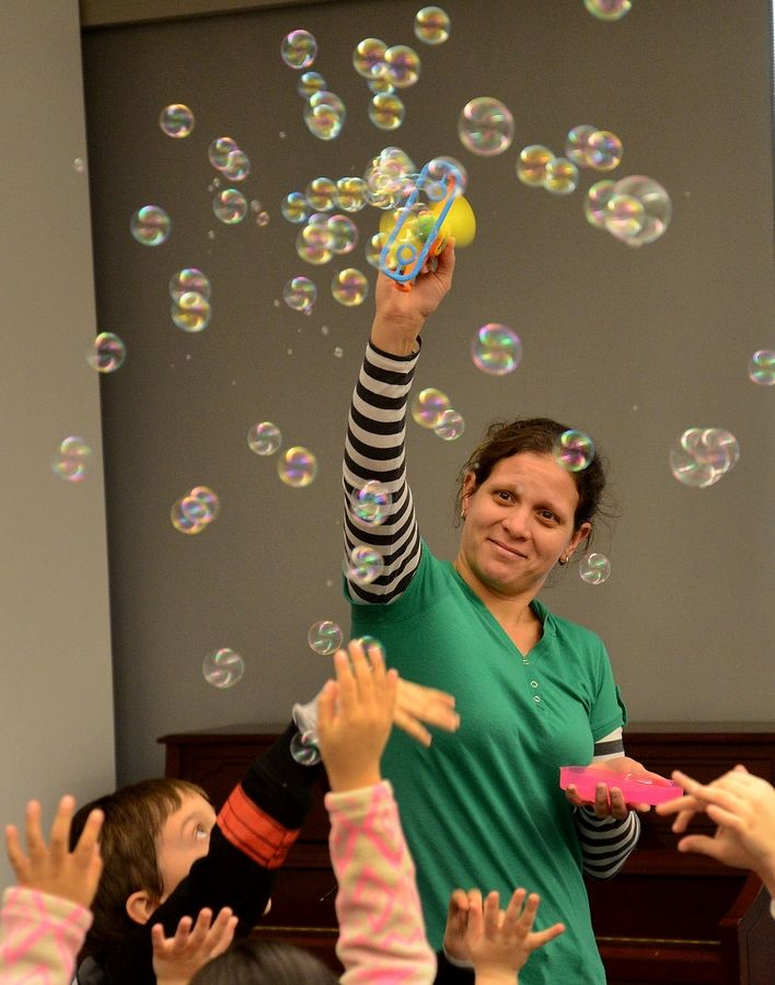 "Stanka Valkanova of Buffalo Grove creates bubbles for the ""The Bubble Medley"" during Jiggle Jam with Jodi Koplin, an interactive ""MusicFest for Children"" Tuesday at the Indian Trails Public Library District in Wheeling."