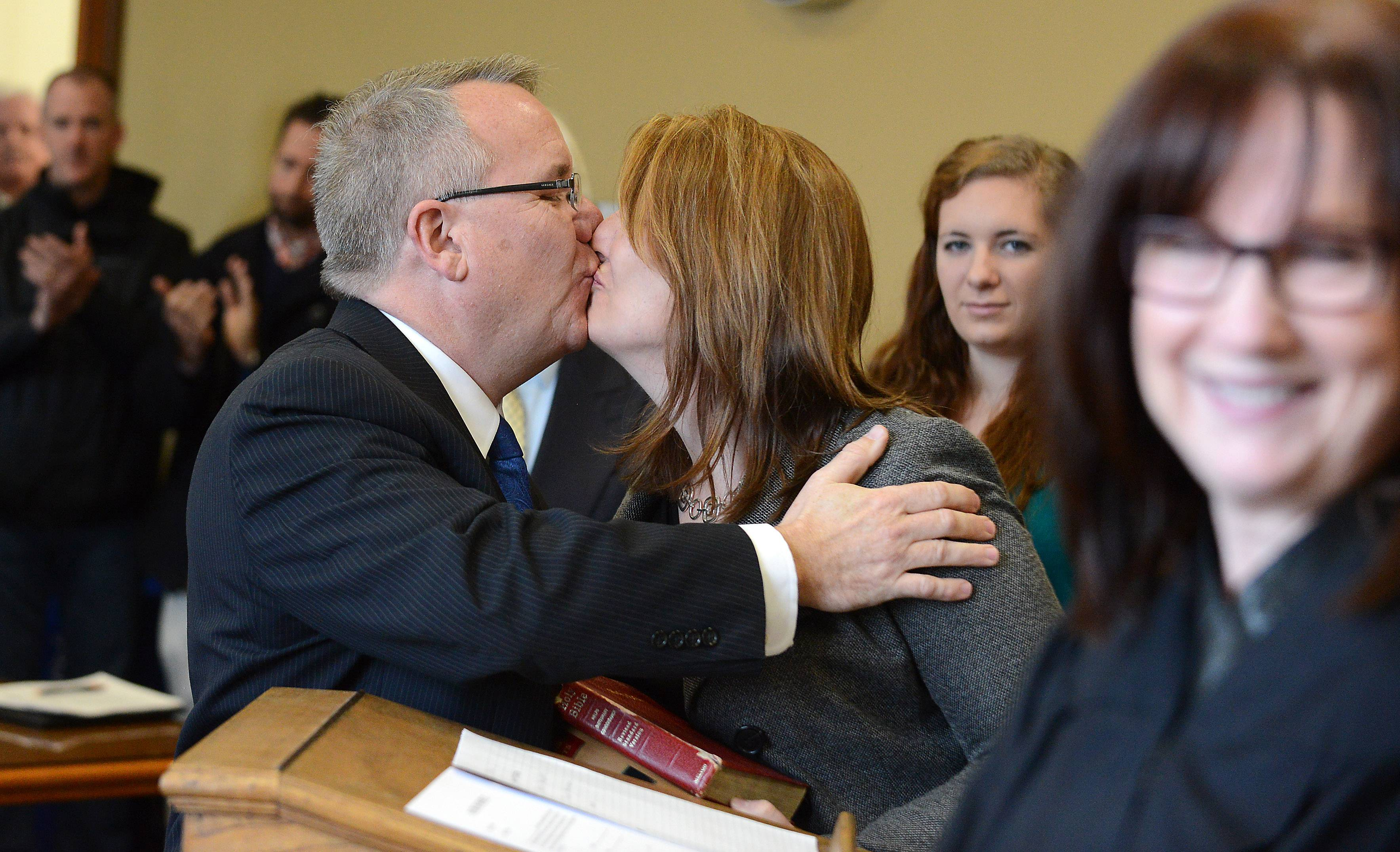 Recently elected state Rep. Steve Andersson kisses his wife, Nanette, after he was sworn in at the Kane County Courthouse in Geneva Friday. He was sworn in by Kane County Associate Judge Linda Abrahamson, right, a law school classmate at Northern Illinois University.