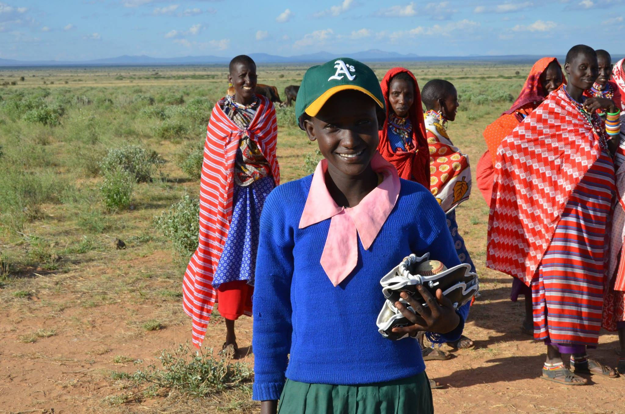 Young woman in Kenya poses with baseball gear donated by Gear for Goals during recent mission trip headed by Northbrook resident Dr. Warren Bruhl. Dreamweaver International