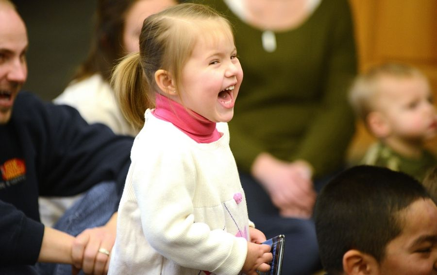 Isabel Mellish, 2, of Batavia is all smiles while watching Juggler Jason Kollum show off his skills Saturday at Messenger Public Library in North Aurora.