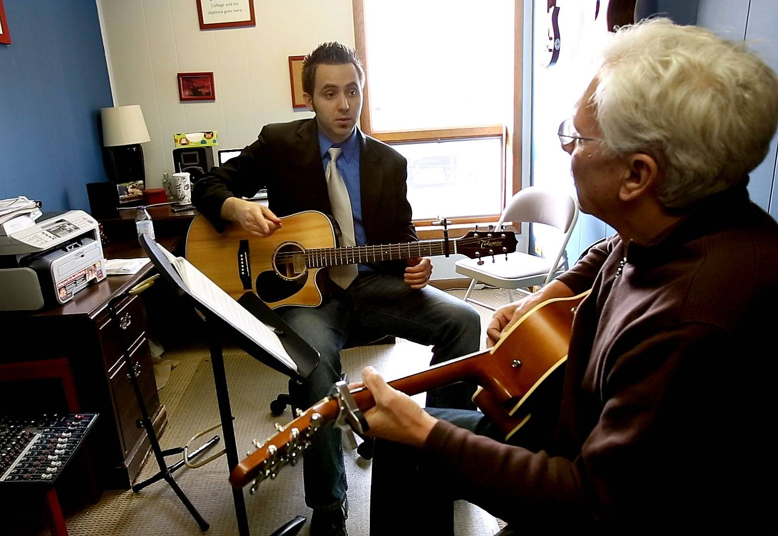 Jerry Evans, left, gives an acoustic guitar lesson to Tom Camden of Wheaton. Evans recently expanded his downtown Wheaton music school to include more space and instructors who can teach guitar, drums, bass, singing, string and wood instruments to children and adults.