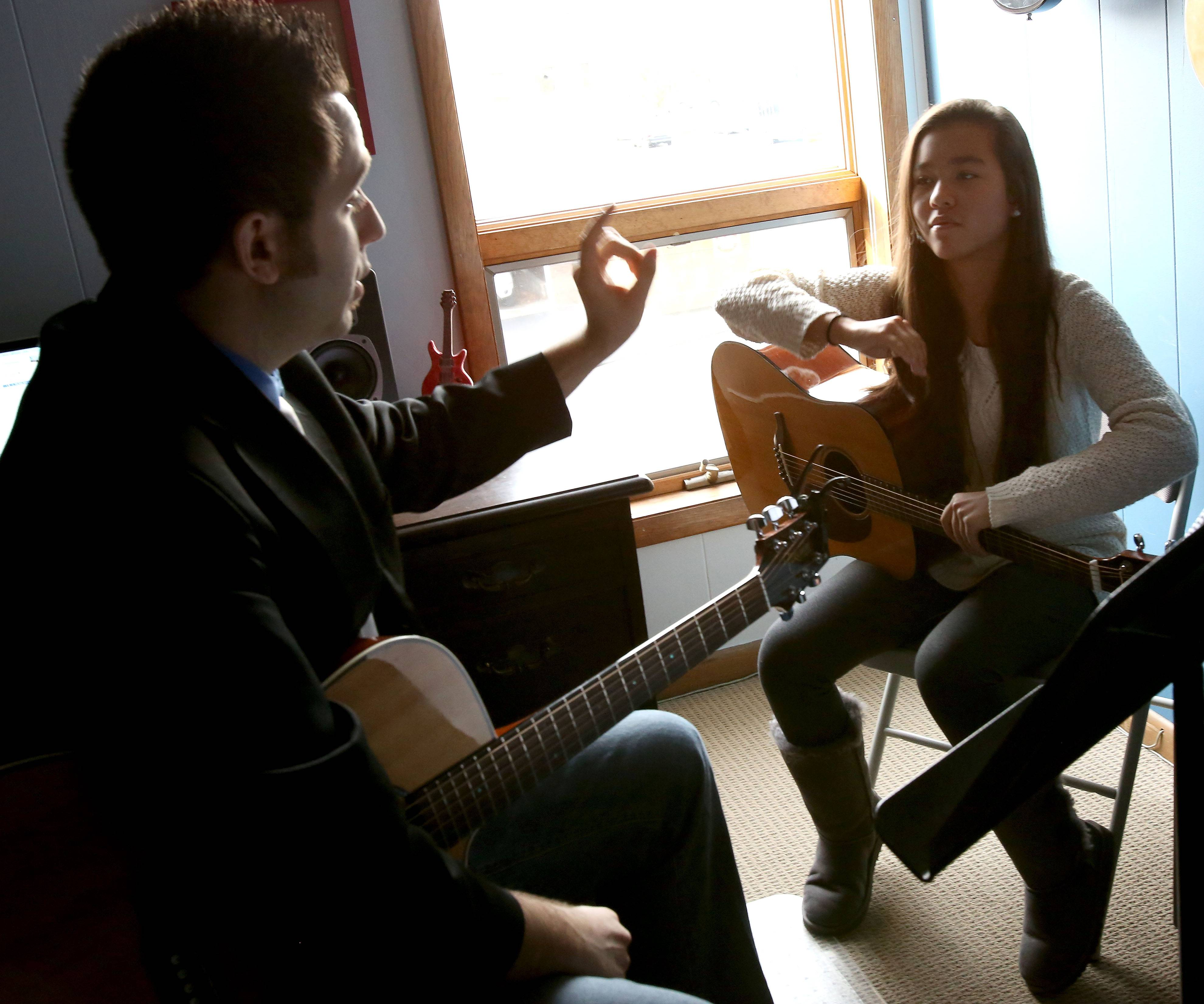 Isabella Hartnett, 13, of Glen Ellyn takes part in an acoustic guitar lesson with Jerry Evans at his recently expanded music school in downtown Wheaton.
