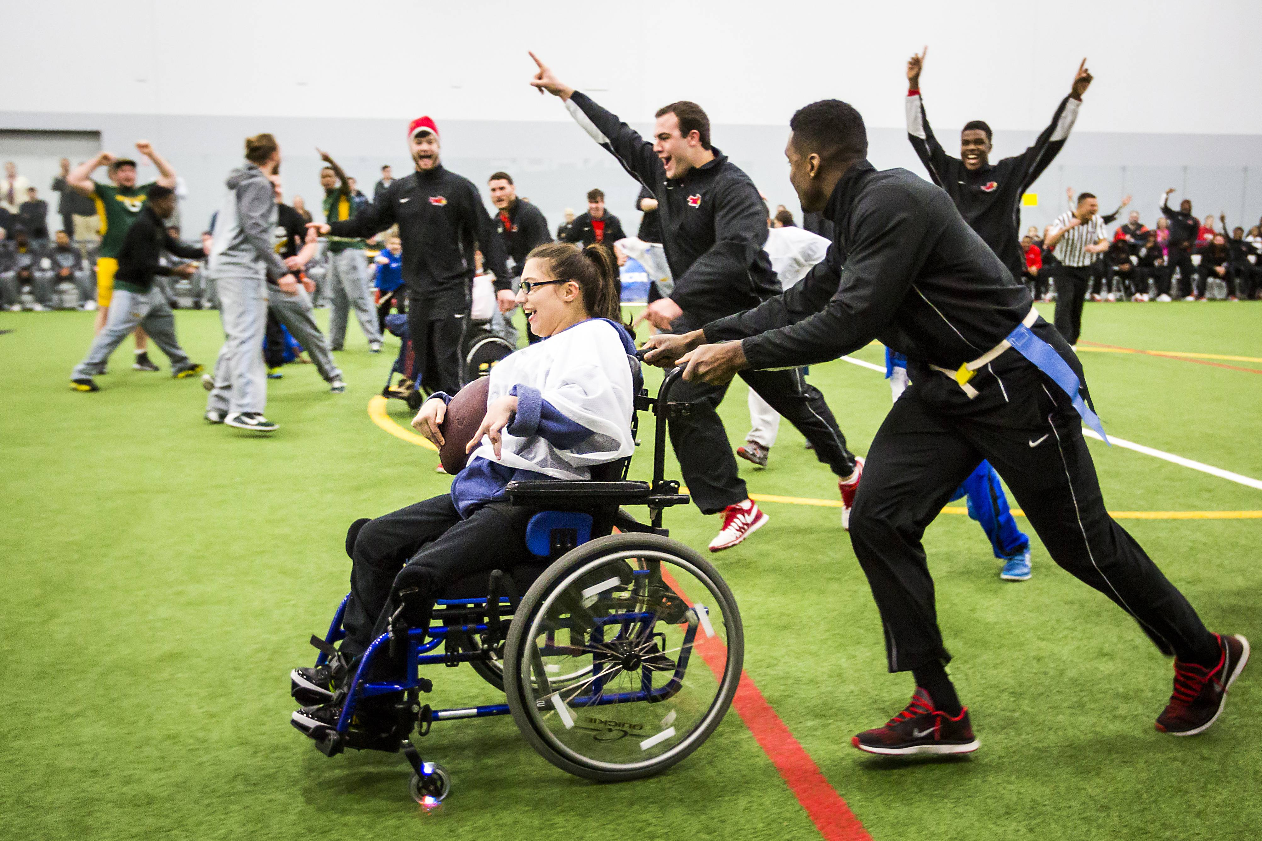 Desi Pacheco gets a push from her buddy, Illinois State running back Jeffrey Lewis, as players from both Illinois State and North Dakota State cheer her on to a touchdown during a Miracle League flag football game Thursday, Jan. 8, 2015, in Frisco, Texas. The game for special needs children is this year's service project for teams participating in the NCAA Football Championship Subdivision title game. (AP Photo/The Dallas Morning News, Smiley N. Pool)