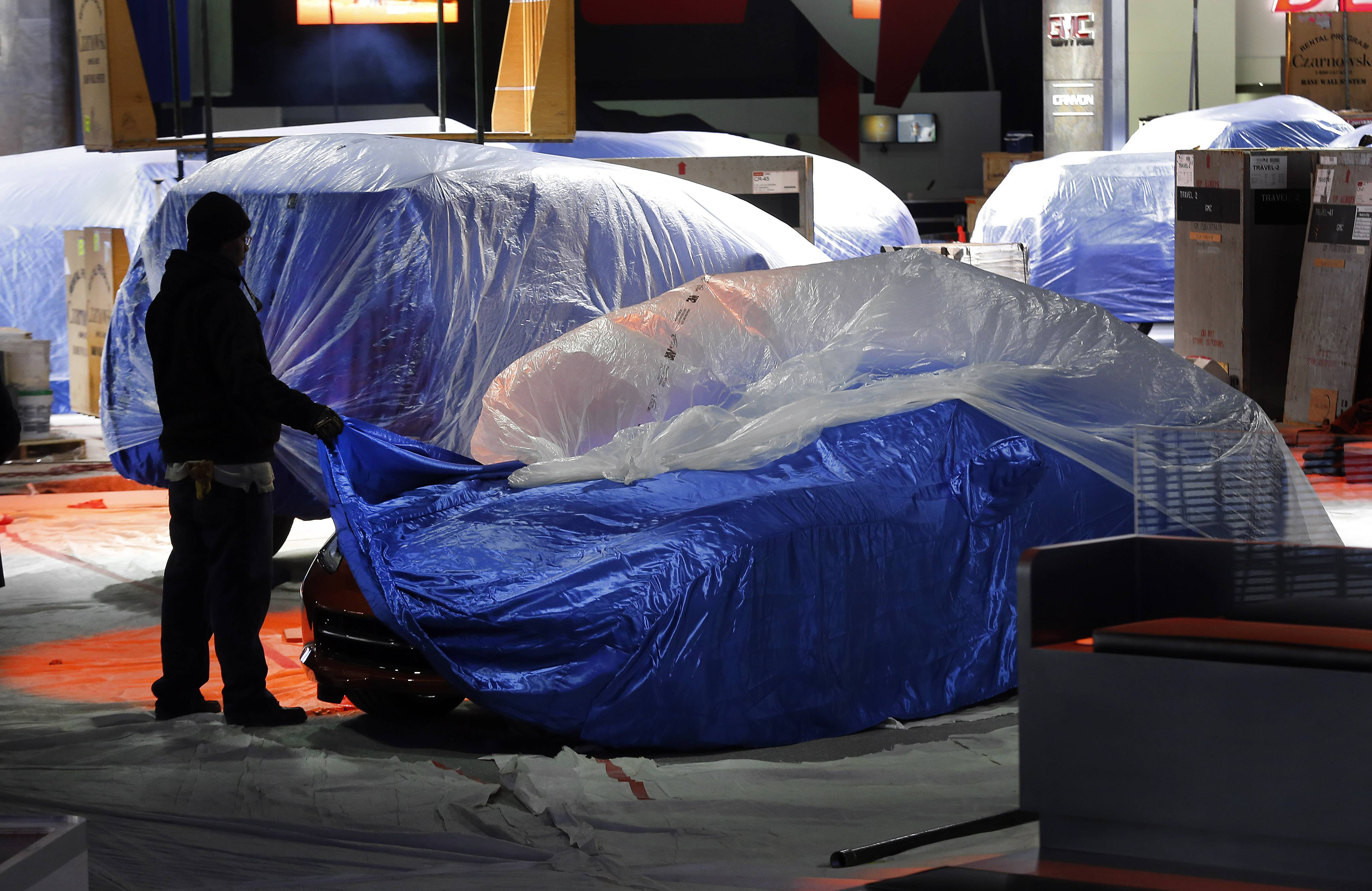 A worker covers a Chevrolet Corvette Stingray during set up Thursday for the North American International Auto Show in Detroit,