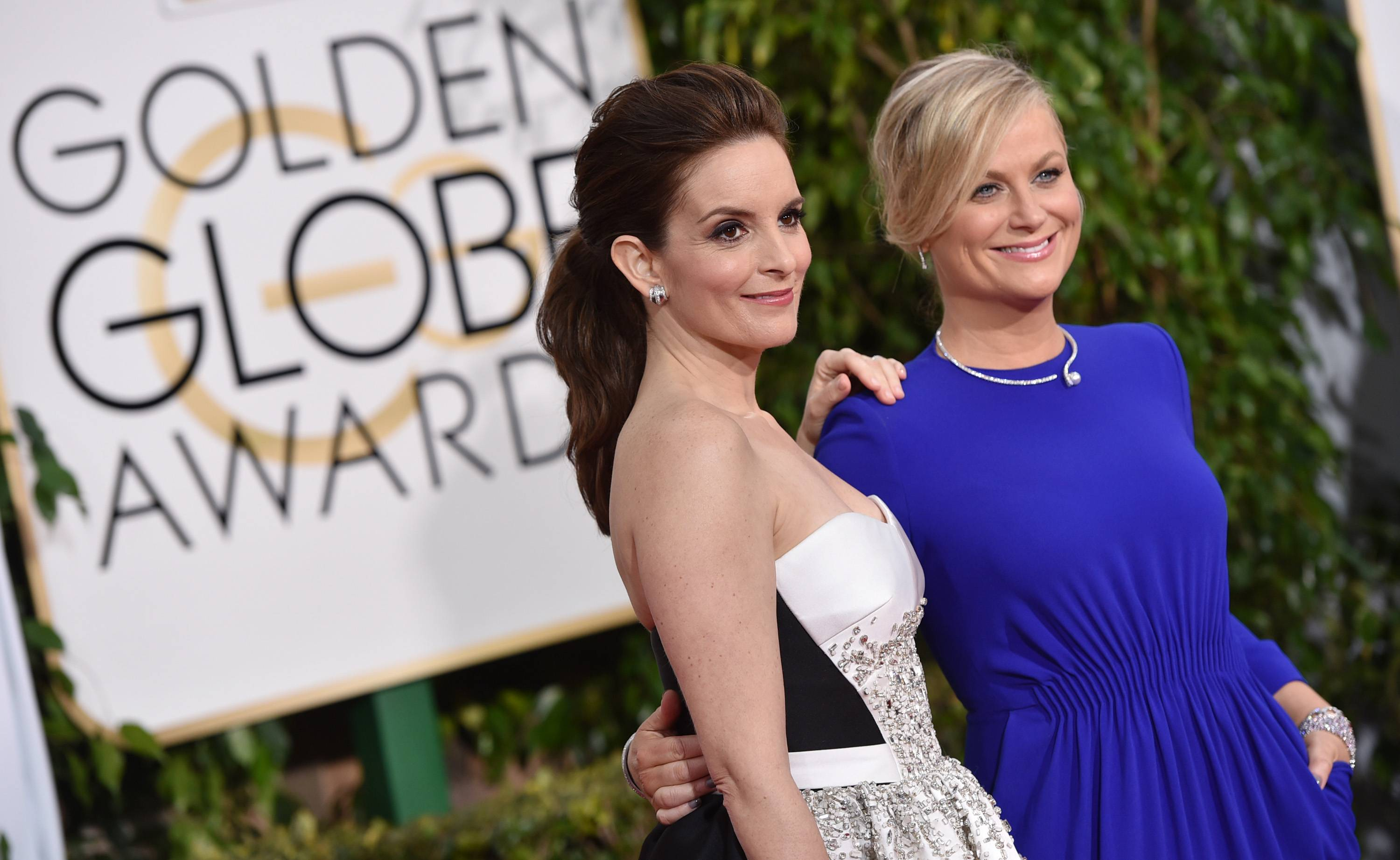 Co-hosts Tina Fey, left, and Amy Poehler arrive at the 72nd annual Golden Globe Awards at the Beverly Hilton Hotel on Sunday.