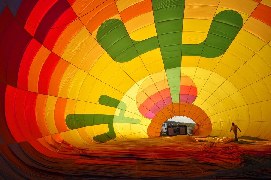 The hot air balloon crew checks the balloon as it is inflated on the desert floor near Scottsdale, Ariz.