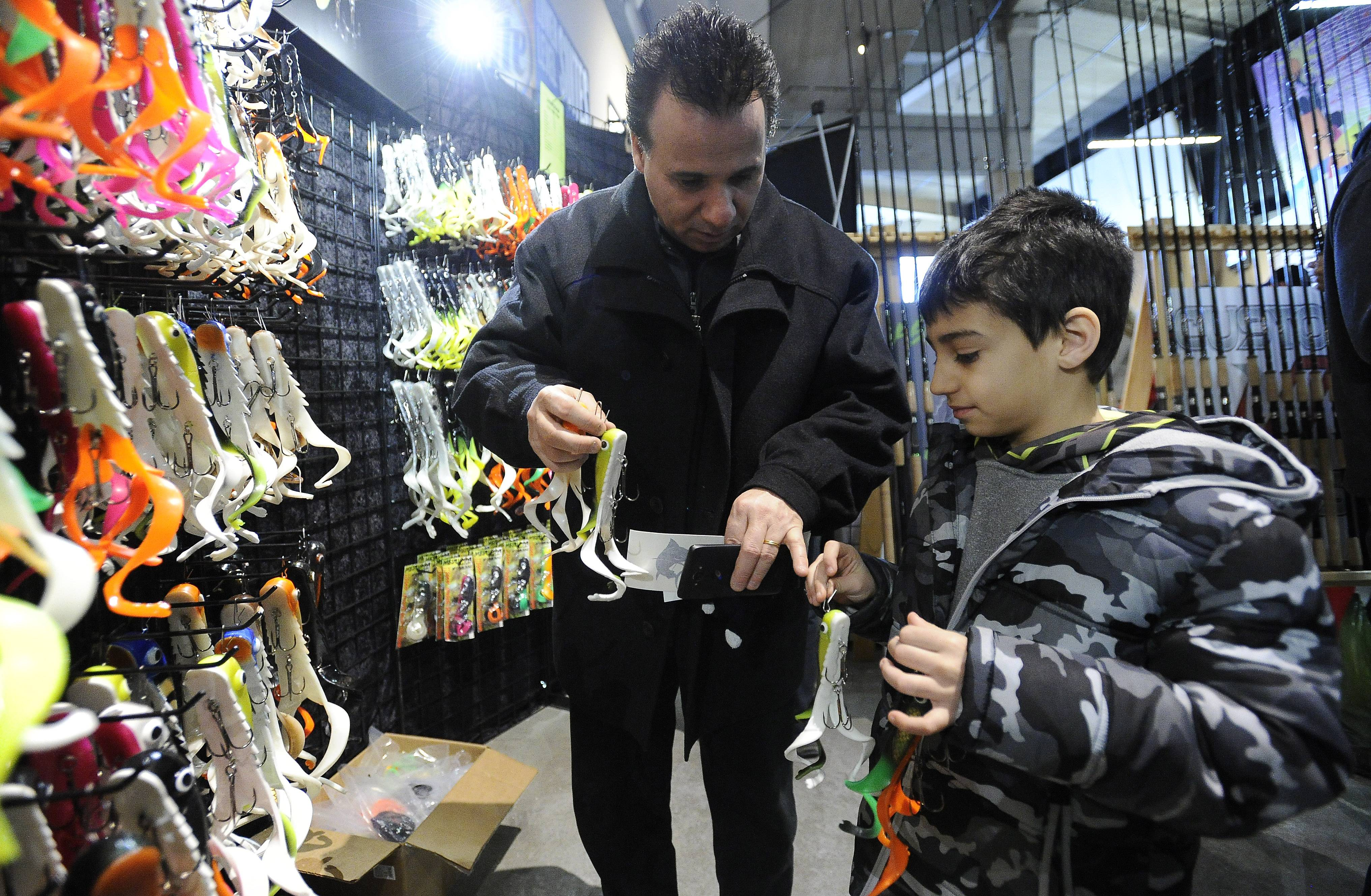 Paul Malek and his son Charlie, 8, of Naperville prepare to purchase different muskie lures on display Saturday at the Chicago Muskie Expo held at the Sears Centre in Hoffman Estates.