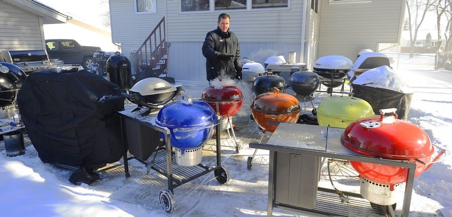 Making sure that none of his 40 Weber grills gets ignored, Kevin Kolman, Grill Master for Weber, fires up a few of his favorites on one of the coldest days of the new year.