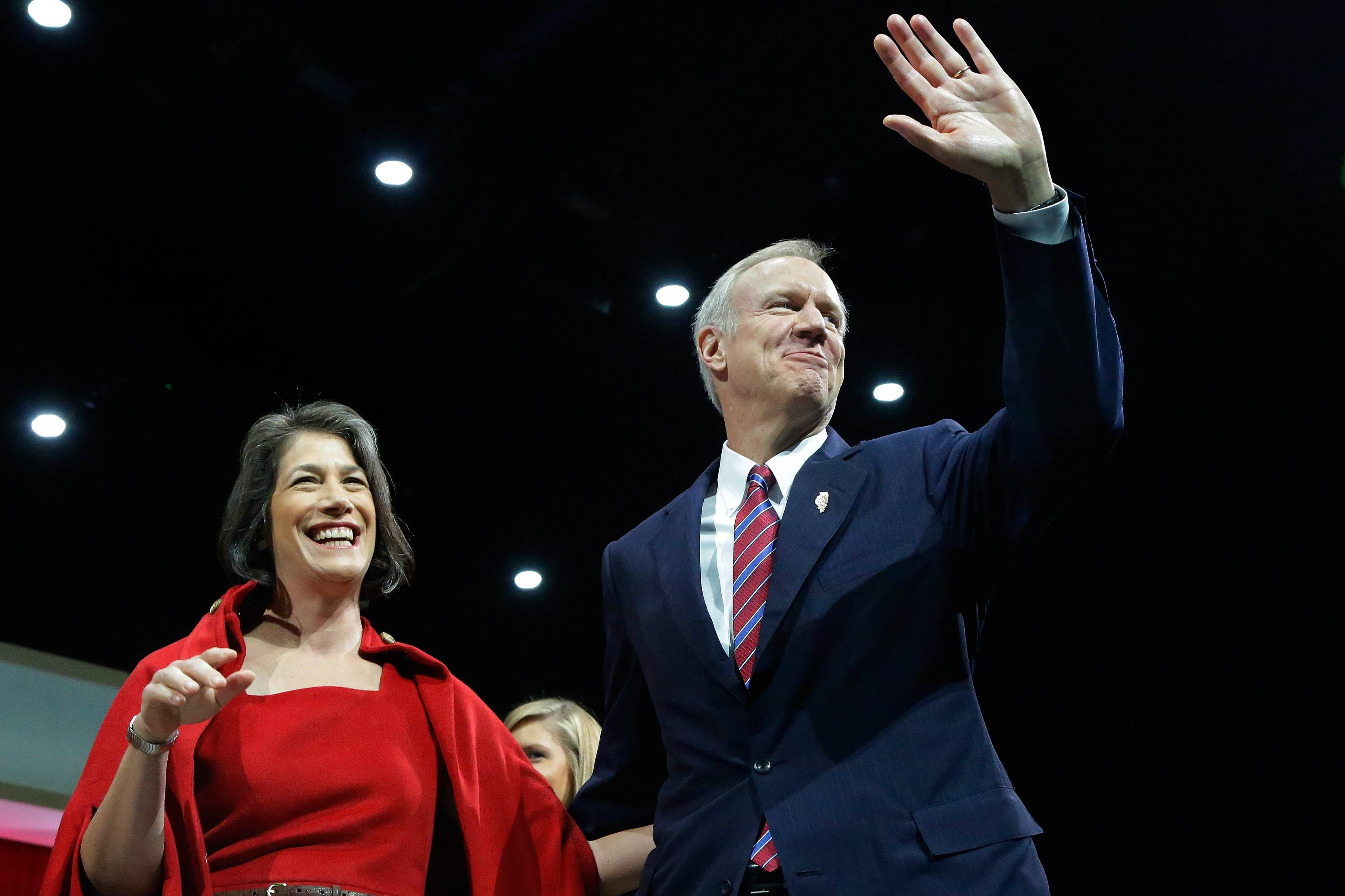 Bruce Rauner and his wife, Diana, wave to supporters after taking the oath of office Monday in Springfield.
