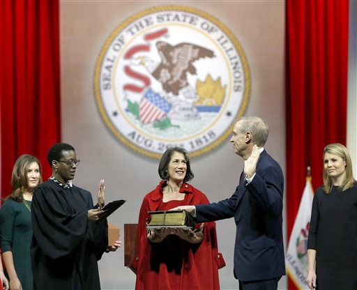Illinois Gov.-elect Bruce Rauner, right, takes the oath of office from Illinois District Judge Sharon Johnson Coleman, left, as his wife, Diana Rauner, holds a Bible, Monday, Jan. 12, 2015, in Springfield, Ill.
