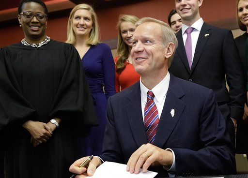 Surrounded by family members and District Judge Sharon Johnson Coleman, left, Illinois Governor Bruce Rauner signs the the oath of office as Illinois' 42nd governor, Monday, Jan. 12, 2015, in Springfield Ill.