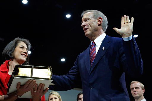 Bruce Rauner takes the oath of office as Illinois' 42nd governor, Monday, Jan. 12, 2015, in Springfield Ill. Rauner's wife Diana, left, is holding the bible.