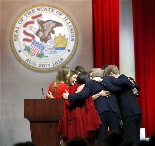 Illinois Gov. Bruce Rauner huddles with his family after being sworn in as Illinois' 42nd governor during ceremonies Monday, Jan. 12, 2015, in Springfield, Ill.