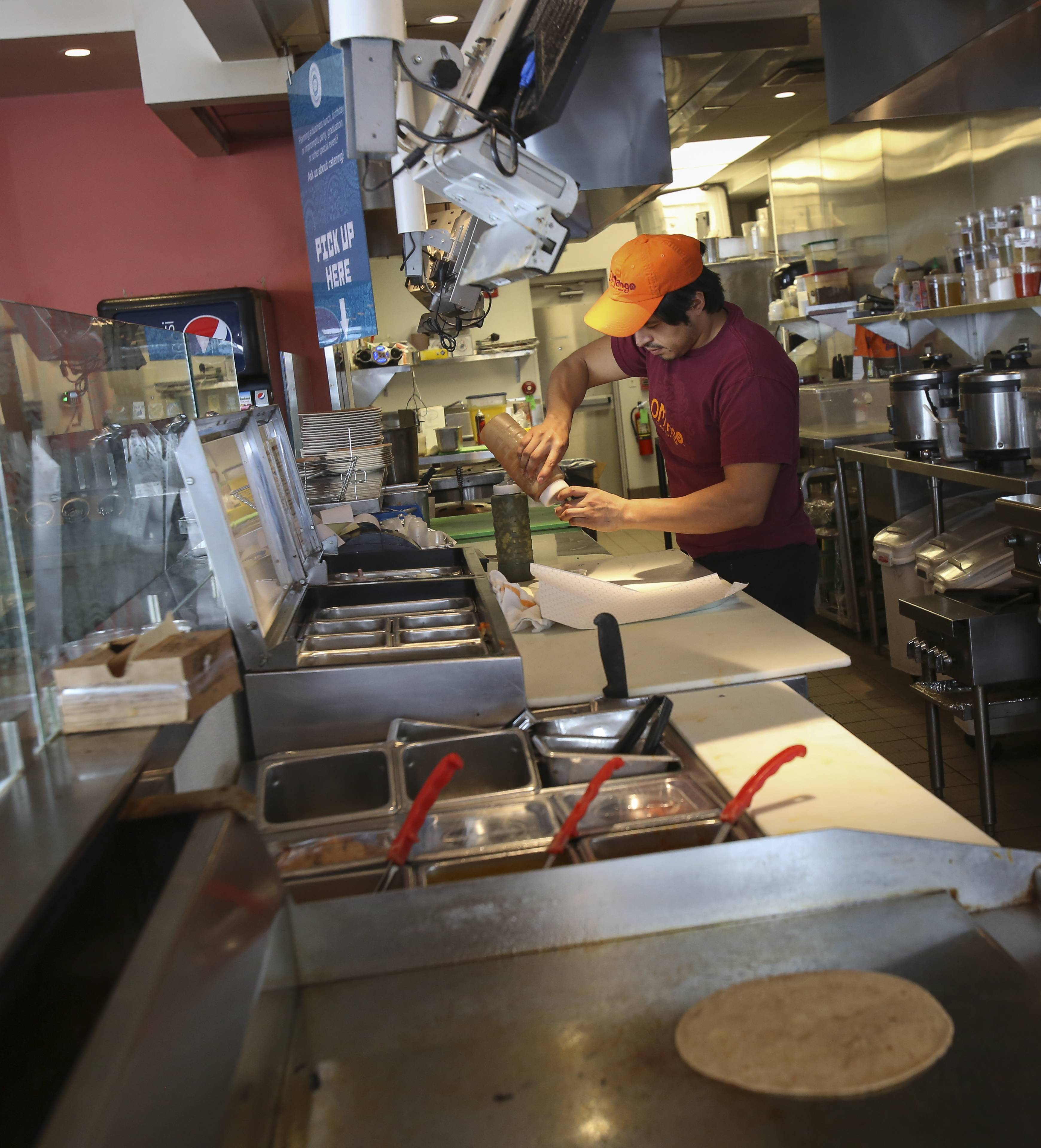 Victor Toxuui, a cook at OMango Flavors of India in Aurora, makes a lunch order Wednesday at the restaurant on Route 59 in Aurora, which recently had to cut its hours, lay off four-part time workers and condense its menu because road construction has led many customers to avoid the area.