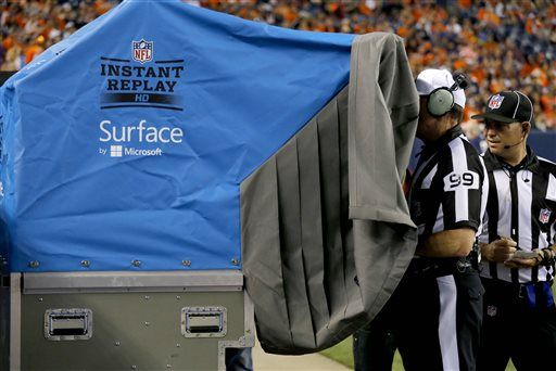 FILE - In this Aug. 7, 2014, file photo, referee Tony Corrente (99) watches an instant replay during the second half of an NFL preseason football game between the Seattle Seahawks and Denver Broncos in Denver. Instant replay in the NFL and other pro sports allows officials to get more calls right. Yet to fans, coaches and players who get to be armchair replay officials, it often feels the other way around.