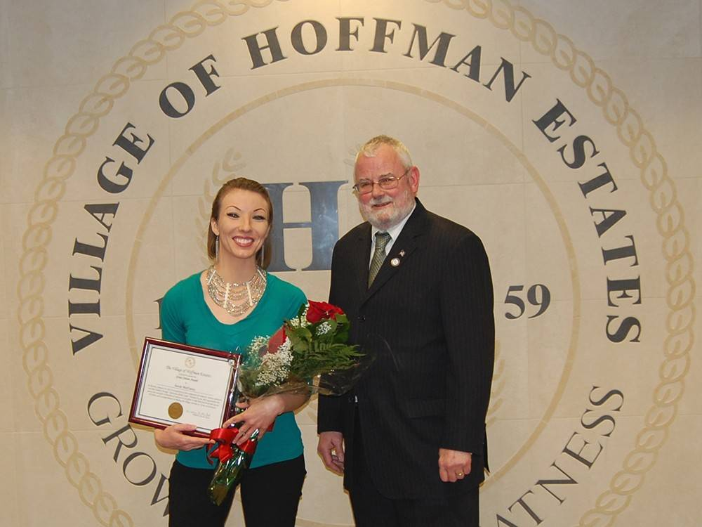 Schaumburg resident Sarah McClarey is recognized by Hoffman Estates Mayor Bill McLeod as a recipient of the village's Great Citizen Award for her activism on behalf of fellow domestic abuse victims.