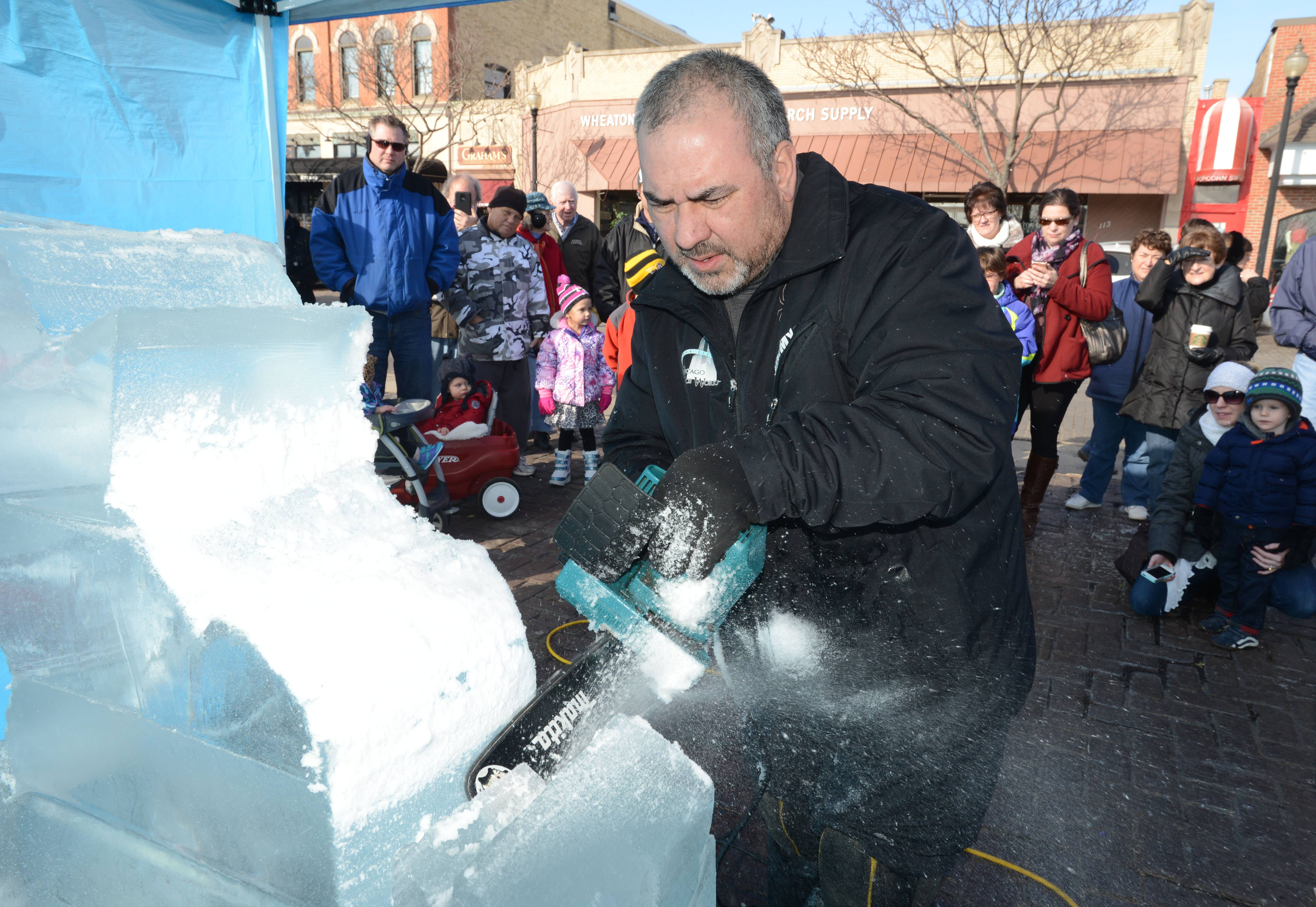 "Jim Bringas, a Chicago Ice Works artist, carves an ice sculpture during the first Ice3 (cubed) Fest in downtown Wheaton Saturday. He carved Olaf, the snowman from Disney's ""Frozen,"" in front of more than 30 parents and children."
