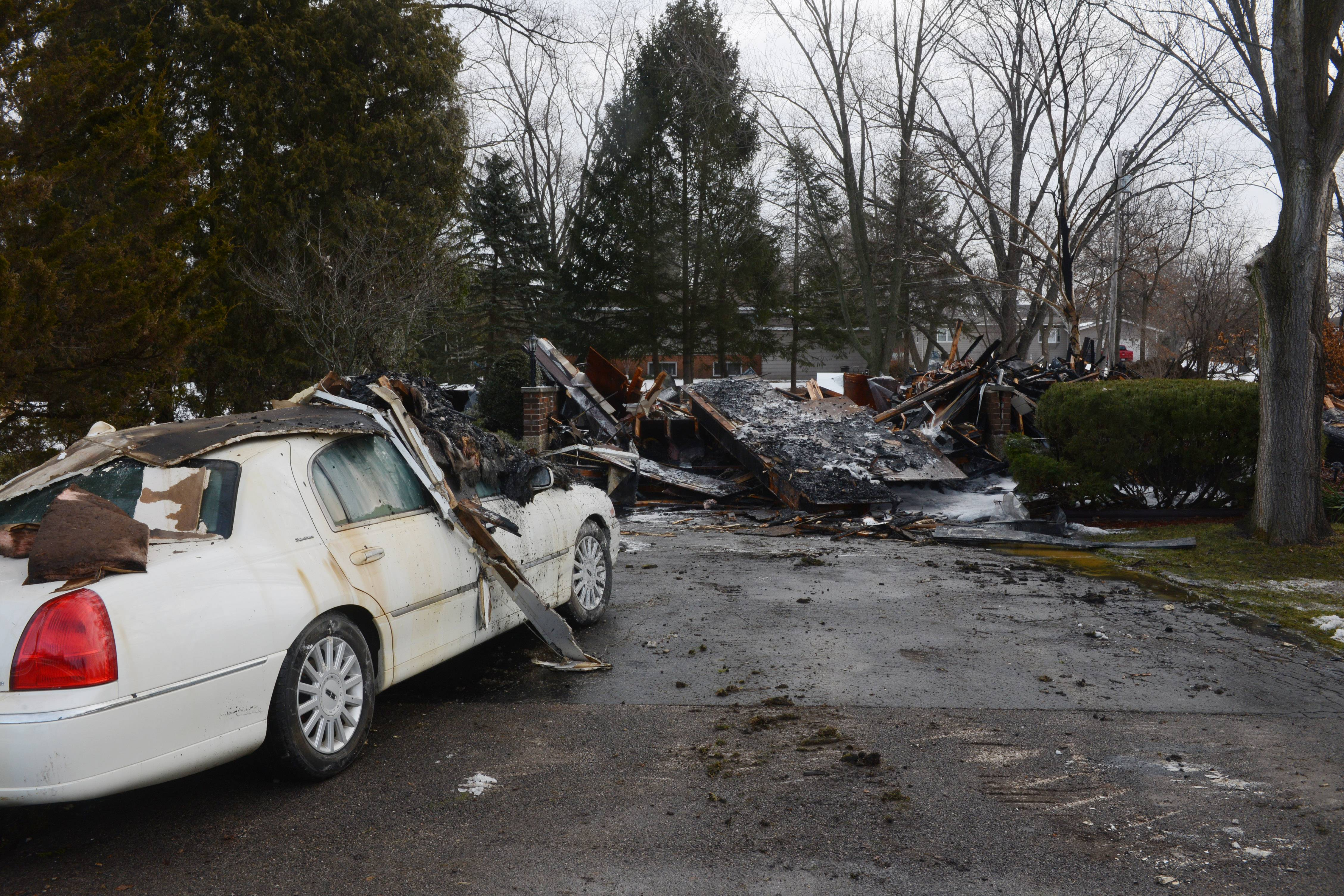 Charred remains of a home and a damaged car at the scene of a fatal fire in the 2100 block of North 21st Street in unincorporated Barrington Saturday morning.