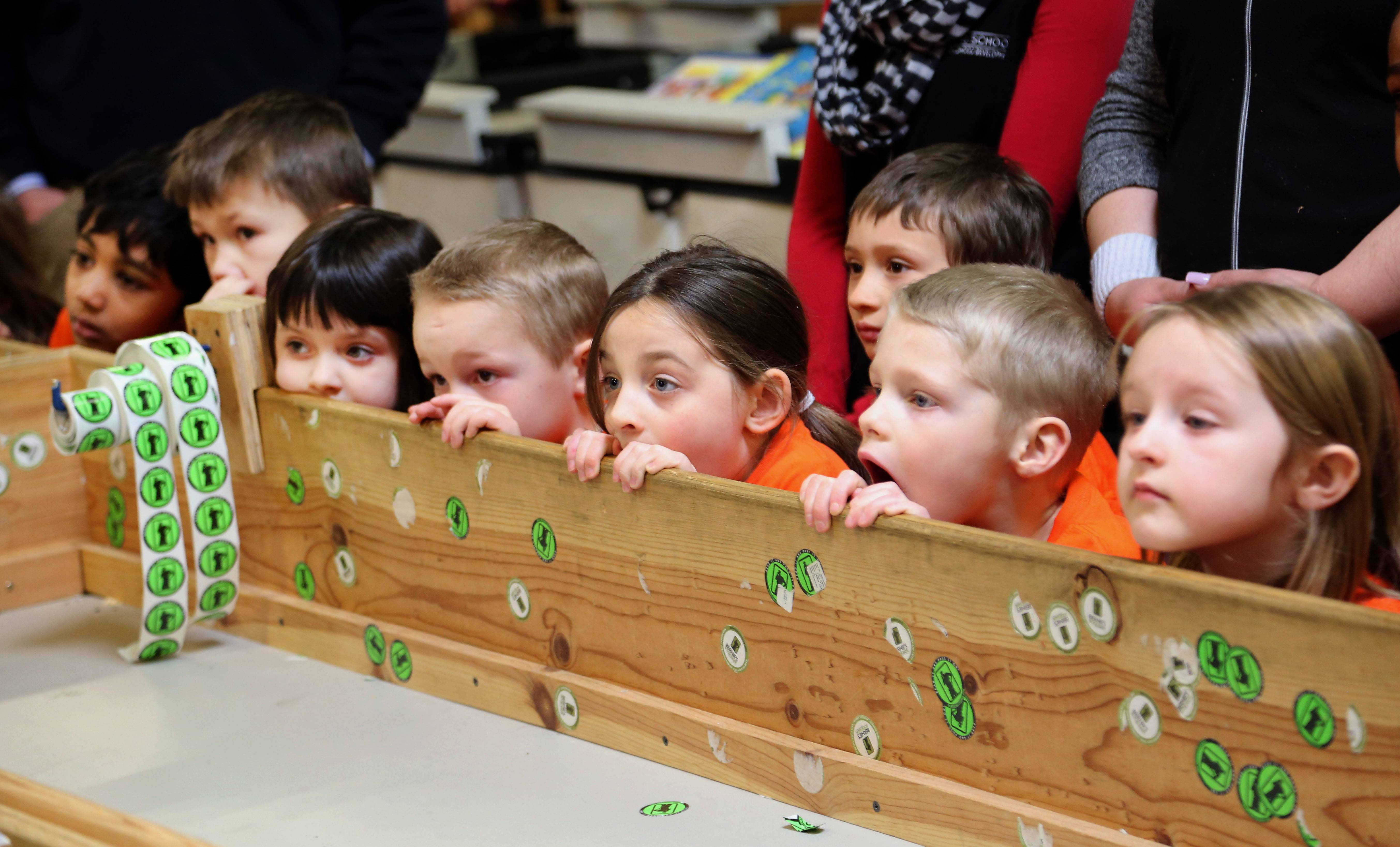 Kindergarteners from The Goddard School in Round Lake listen intently as they watch a video during a volunteer day at Bernie's Book Bank in Lake Forest Friday.