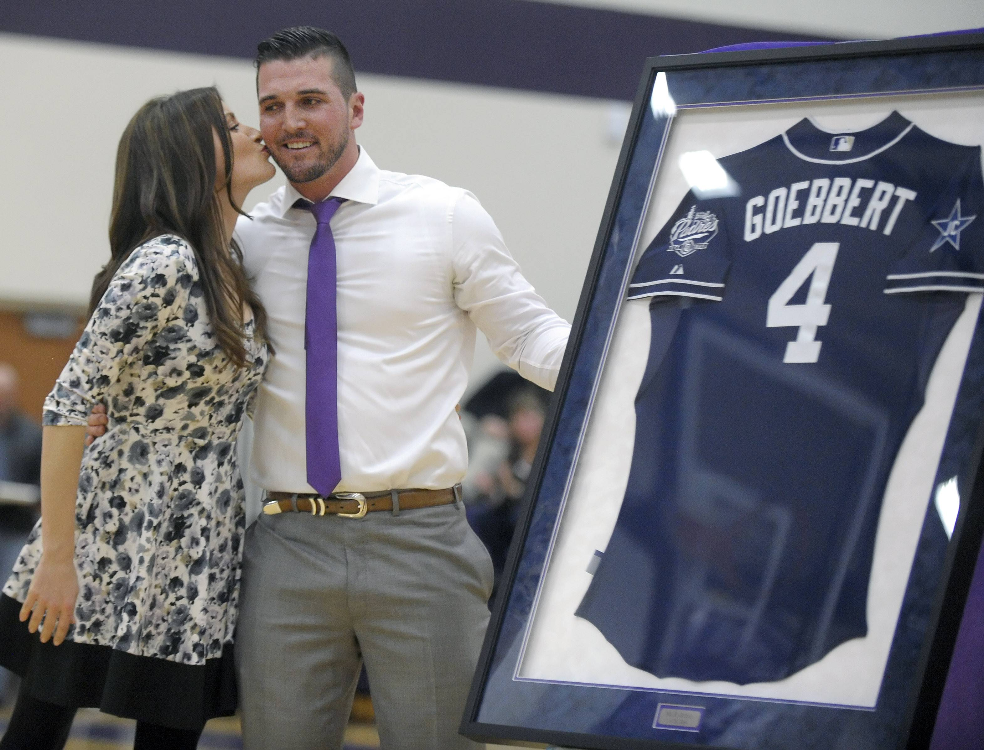Hampshire High School graduate Jake Goebbert of Pingree Grove gets a peck on the cheek from his wife, Heather, after unveiling his San Diego Padres baseball jersey before the start of the boys varsity basketball game Saturday.