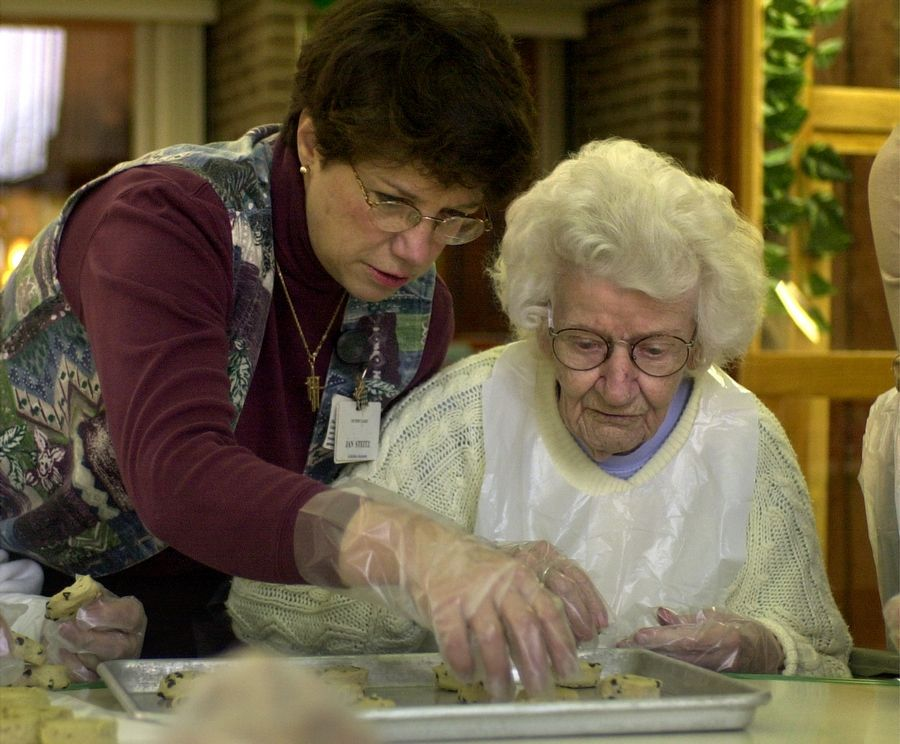A Victory Lakes Continuing Care Center activity assistant helps a resident make cookies at the Lindenhurst facility.