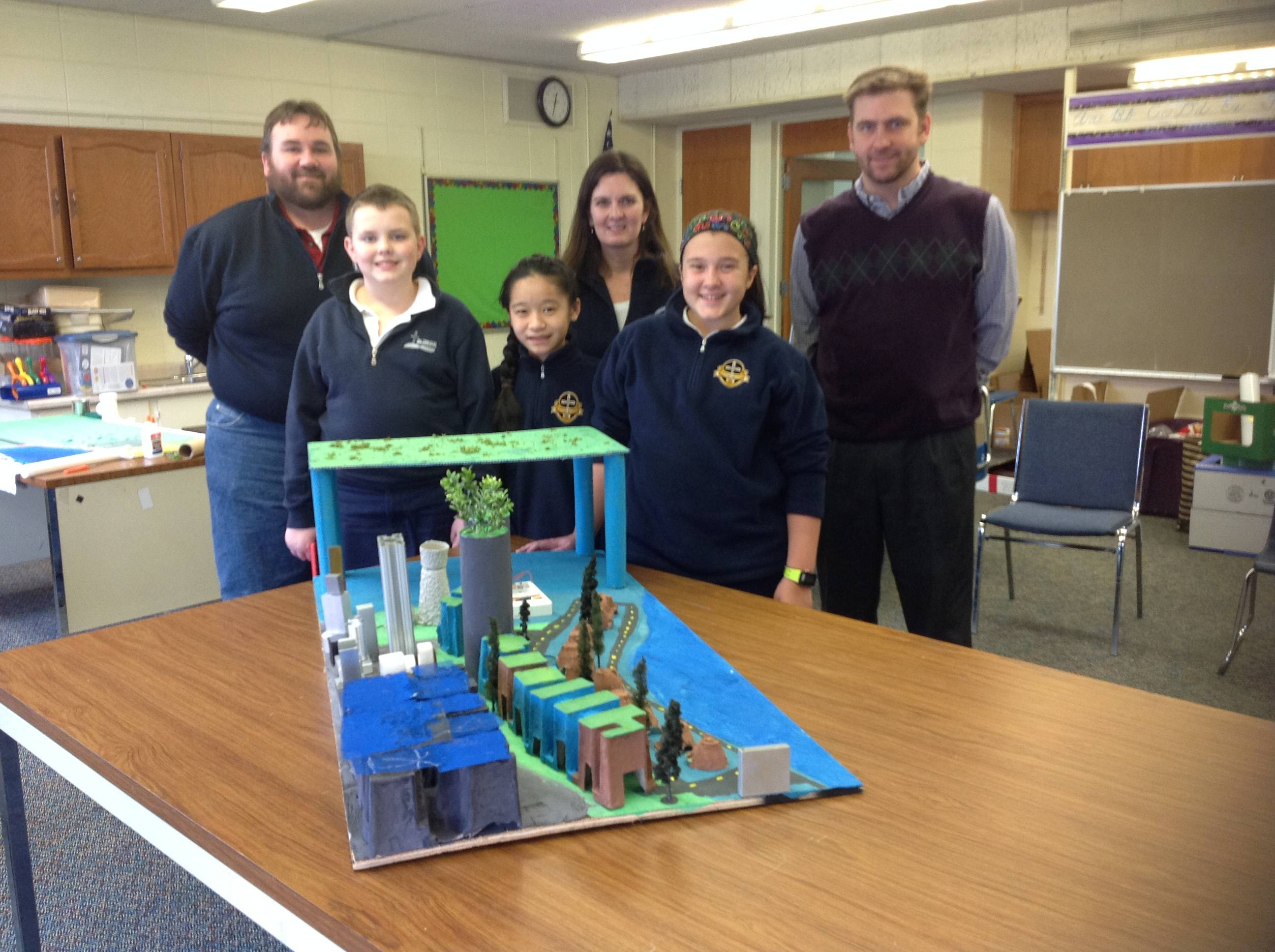St. Hubert Catholic School students and mentors proudly display their physical model of the city they developed which included a nuclear power plant and elevated farms as well as buildings that utilized solar panels and green roofing.mlarson