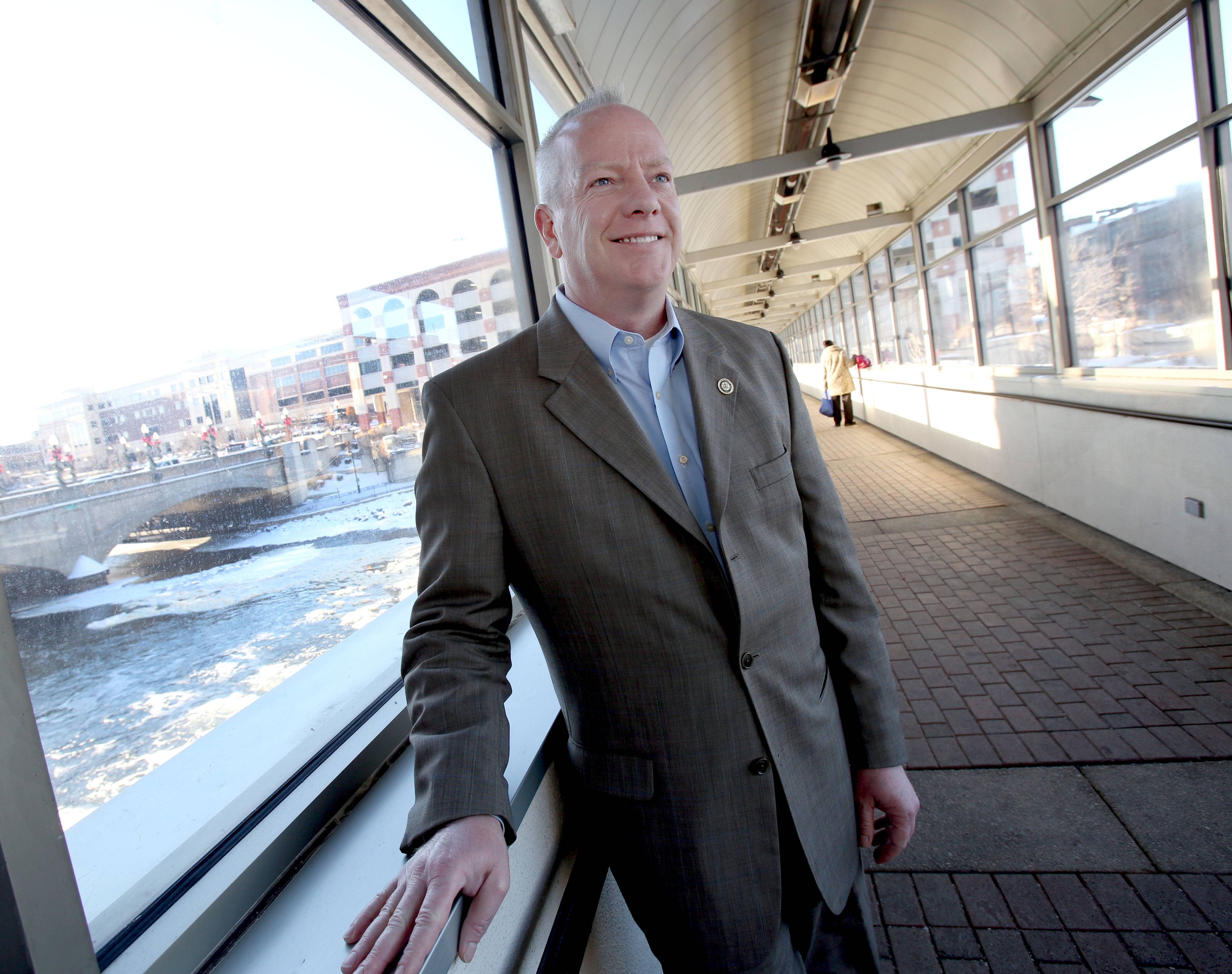 Joe Henning, head of the Aurora Regional Chamber of Commerce since 2005, stands in the walkway that goes over the river in the heart of the downtown of his beloved city.