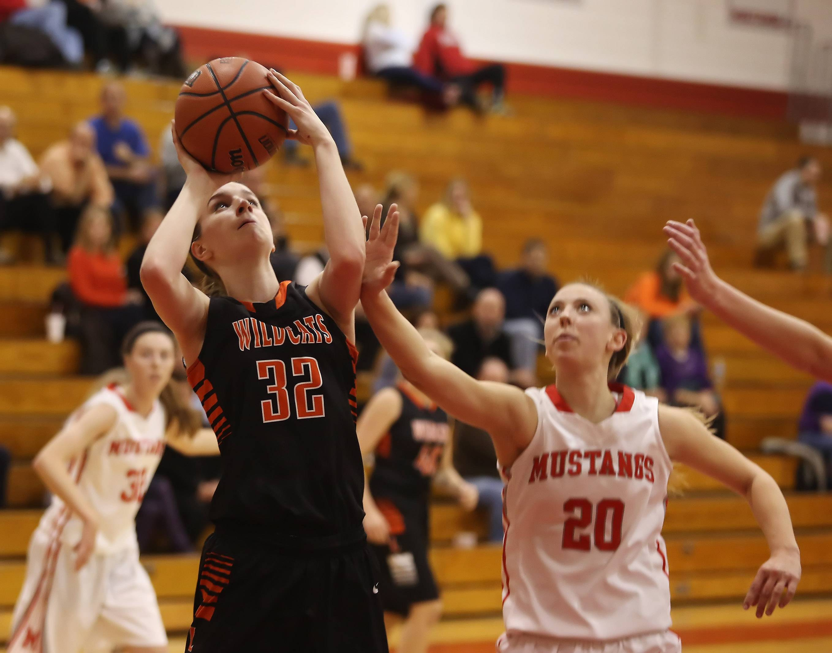 Libertyville forward Caroline Frea takes a shot over Mundelein forward Natalie Busscher.