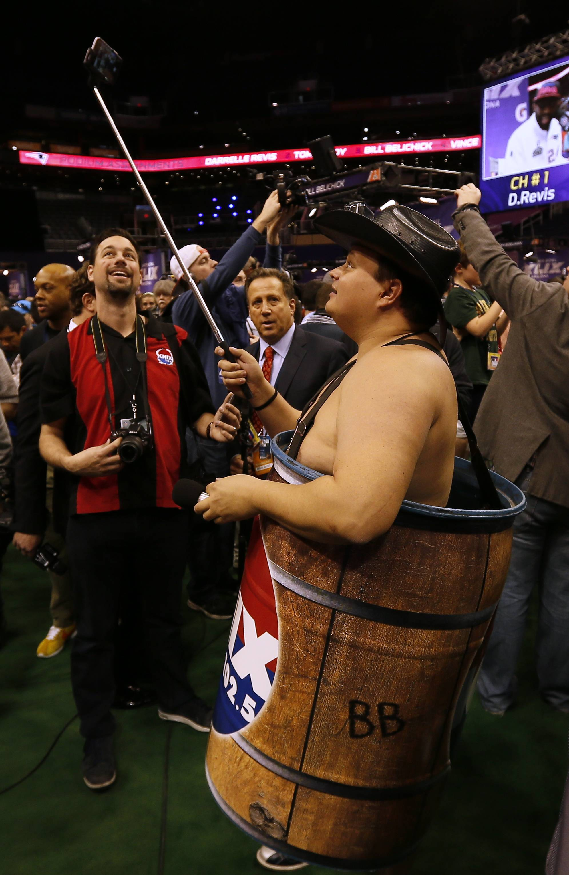 A radio station reporter, wearing a barrel, takes selfies during media day for NFL Super Bowl XLIX football game Tuesday, Jan. 27, 2015, in Phoenix.