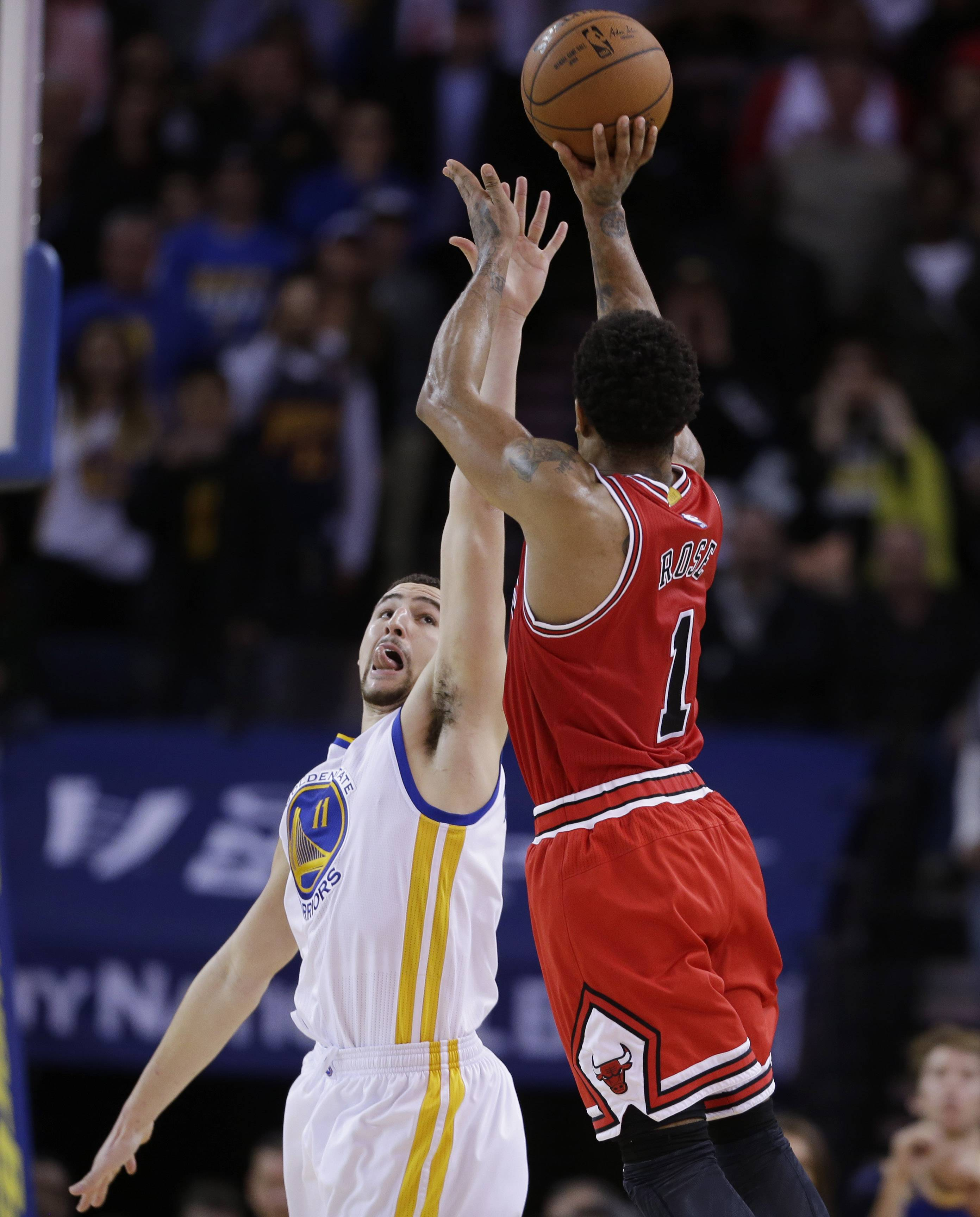 Chicago Bulls' Derrick Rose, right, hits the go-ahead shot over Golden State Warriors' Klay Thompson during overtime of an NBA basketball game Tuesday, Jan. 27, 2015, in Oakland, Calif. Chicago won 113-111. (AP Photo/Marcio Jose Sanchez)