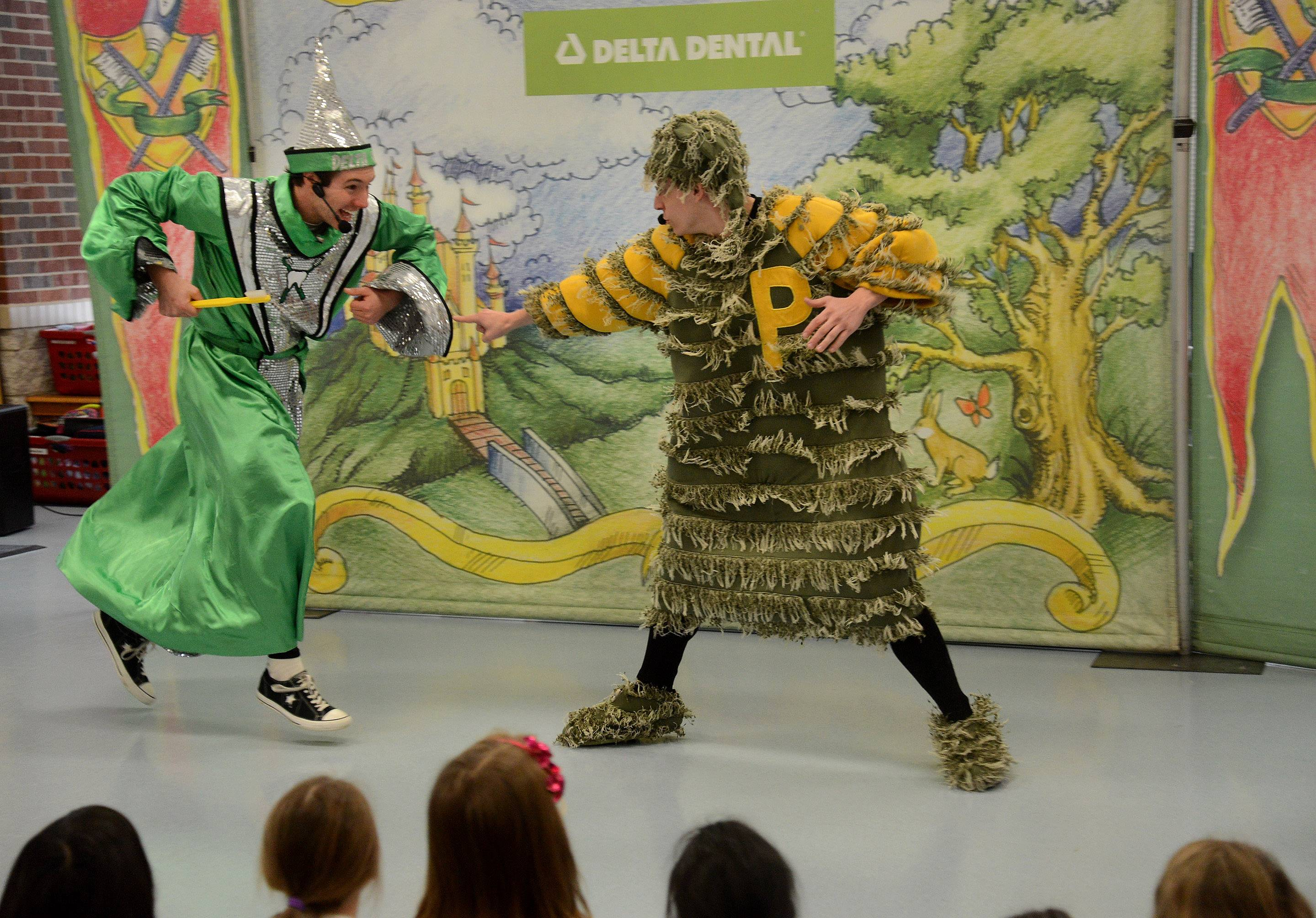 "Tooth Wizard, left, and PlaqueMan battle for the health of kids' teeth Thursday during the Delta Dental of Illinois Foundation's ""Land of Smiles"" presentation at Brentwood Elementary School in Des Plaines."