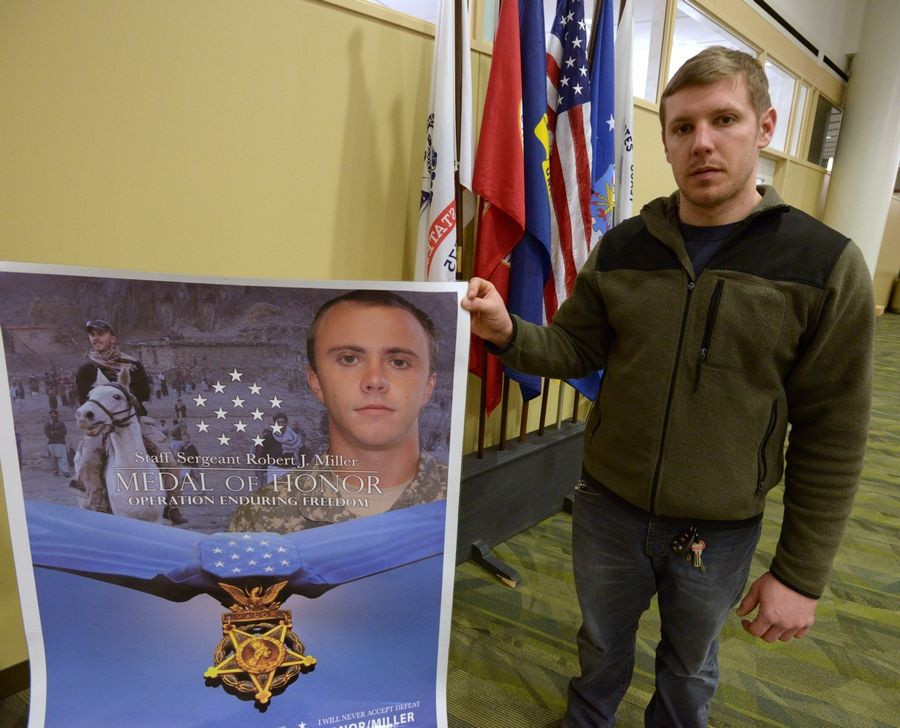 Veteran Bobby Kaye of St. Charles holds a poster honoring Medal of Honor recipient Robert J. Miller of Wheaton. Kaye and others want the College of DuPage's Homeland Security Education Center to be named after Miller instead of College President Robert Breuder.