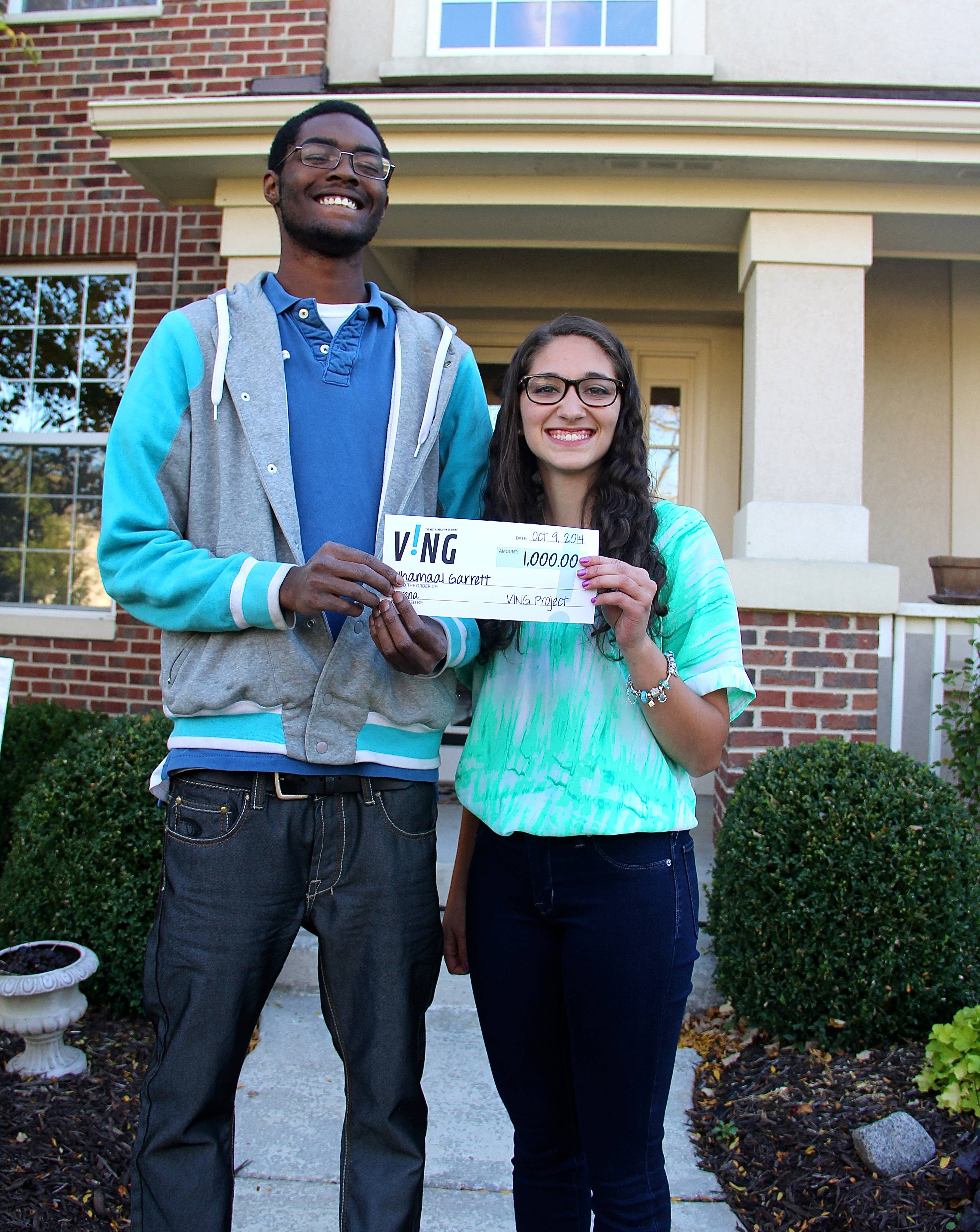 VING Project participant Serena Panos, right, 16, delivers a surprise check for $1,000 to her chosen recipient, Jhamaal Grant, outside of her neighbor's house.
