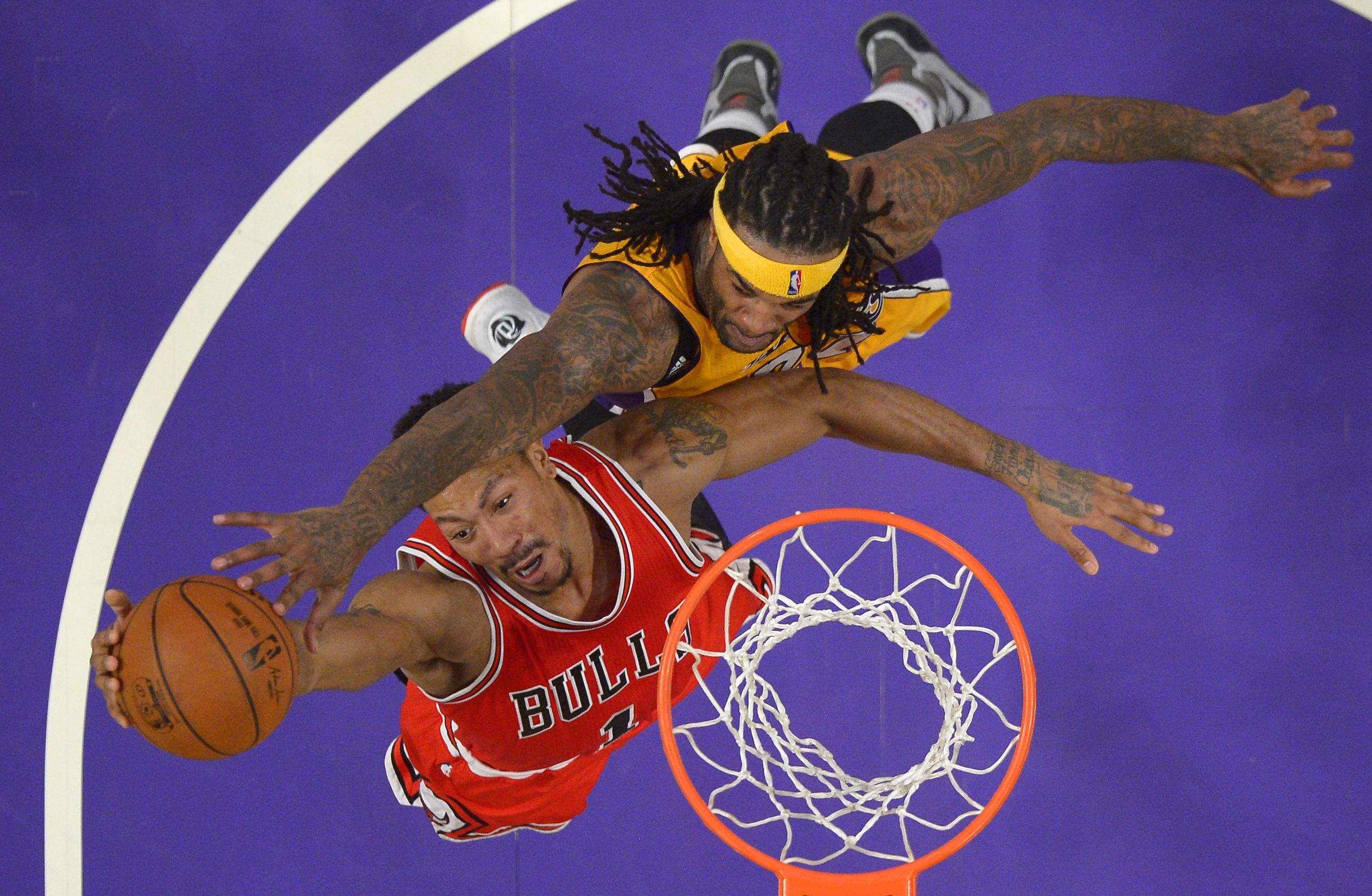 The Bulls' Derrick Rose, here trying a shot under pressure from the Lakers' Jordan Hill, hit only 7 of 26 shots for 17 points including some ill-advised misses from long range Thursday in a 123-118 double overtime loss in Los Angeles.