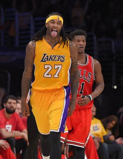 Los Angeles Lakers center Jordan Hill, left, reacts as Chicago Bulls guard Jimmy Butler looks on after scoring in the second overtime of an NBA basketball game, Thursday, Jan. 29, 2015, in Los Angeles. The Lakers won 123-118. (AP Photo/Mark J. Terrill)