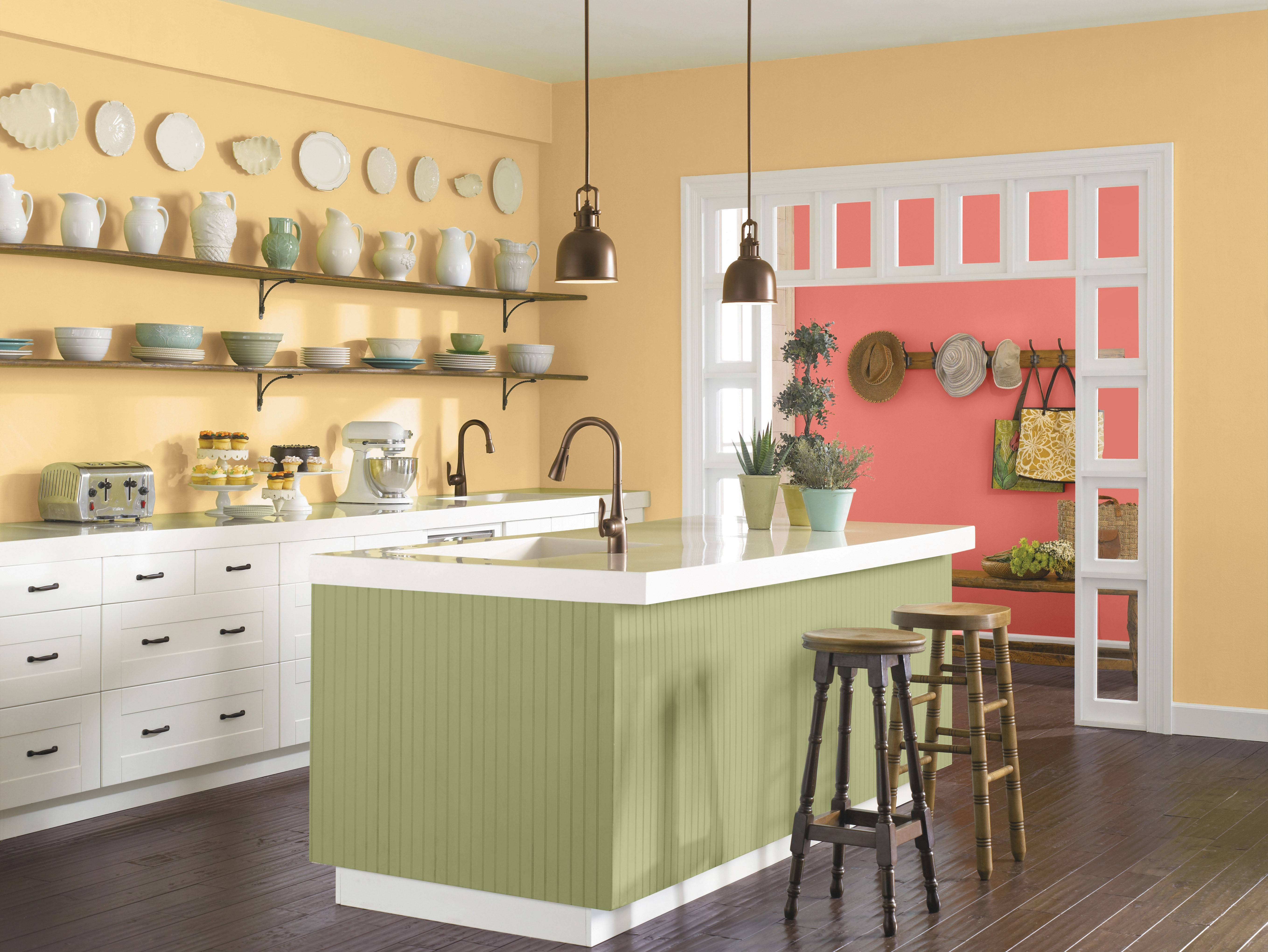 Sherwin-Williams chose Coral Reef, a mix of pink and orange, as its Color of the Year. Here this color is used next to a yellow kitchen with olive cabinetry.