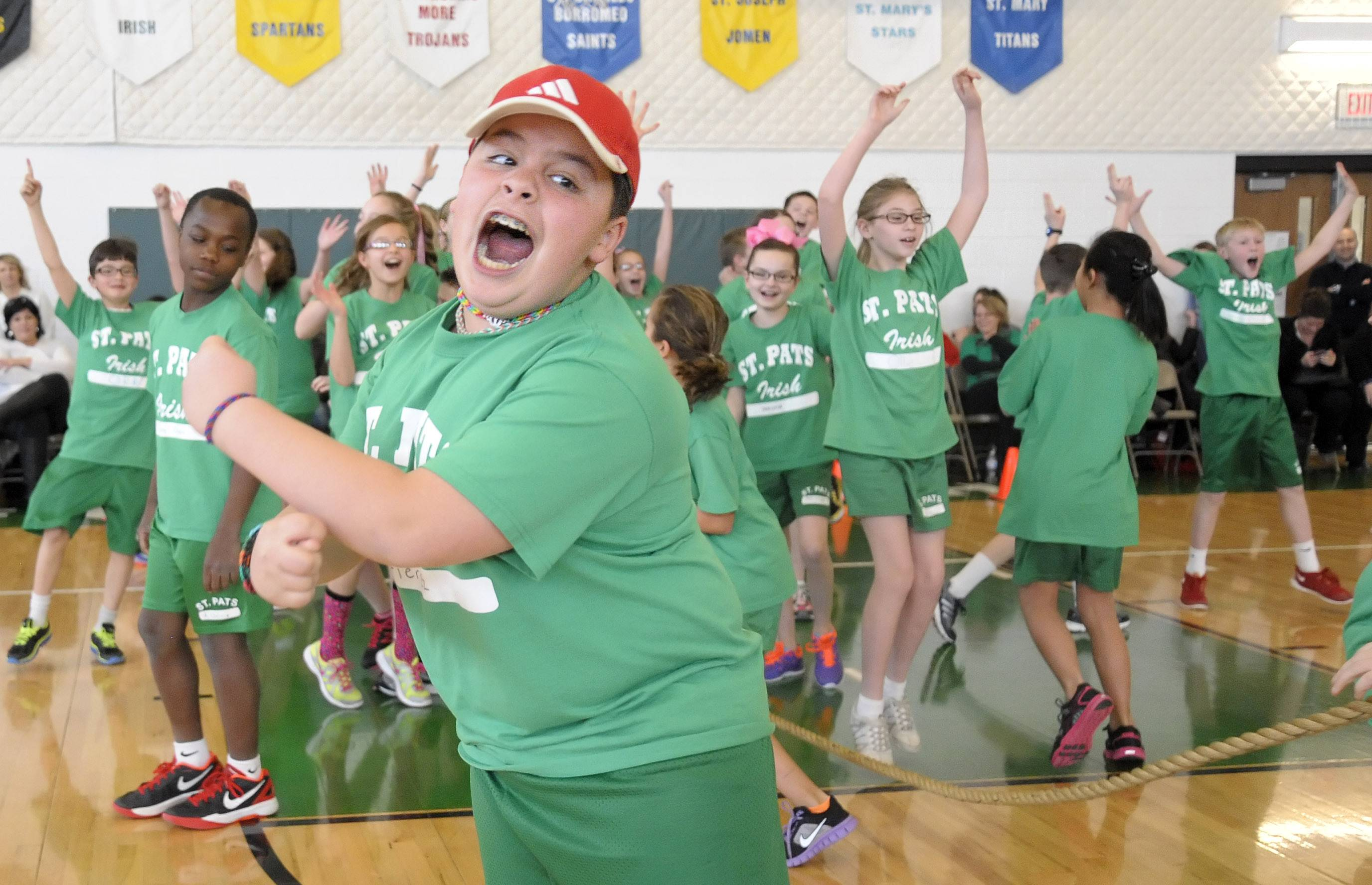 "Lucas Gutierrez, 11, of St. Charles, and teammates celebrate their victory in the ""Tug of War"" competition at St. Patrick School in St. Charles during their Catholic Schools Week assembly Wednesday."