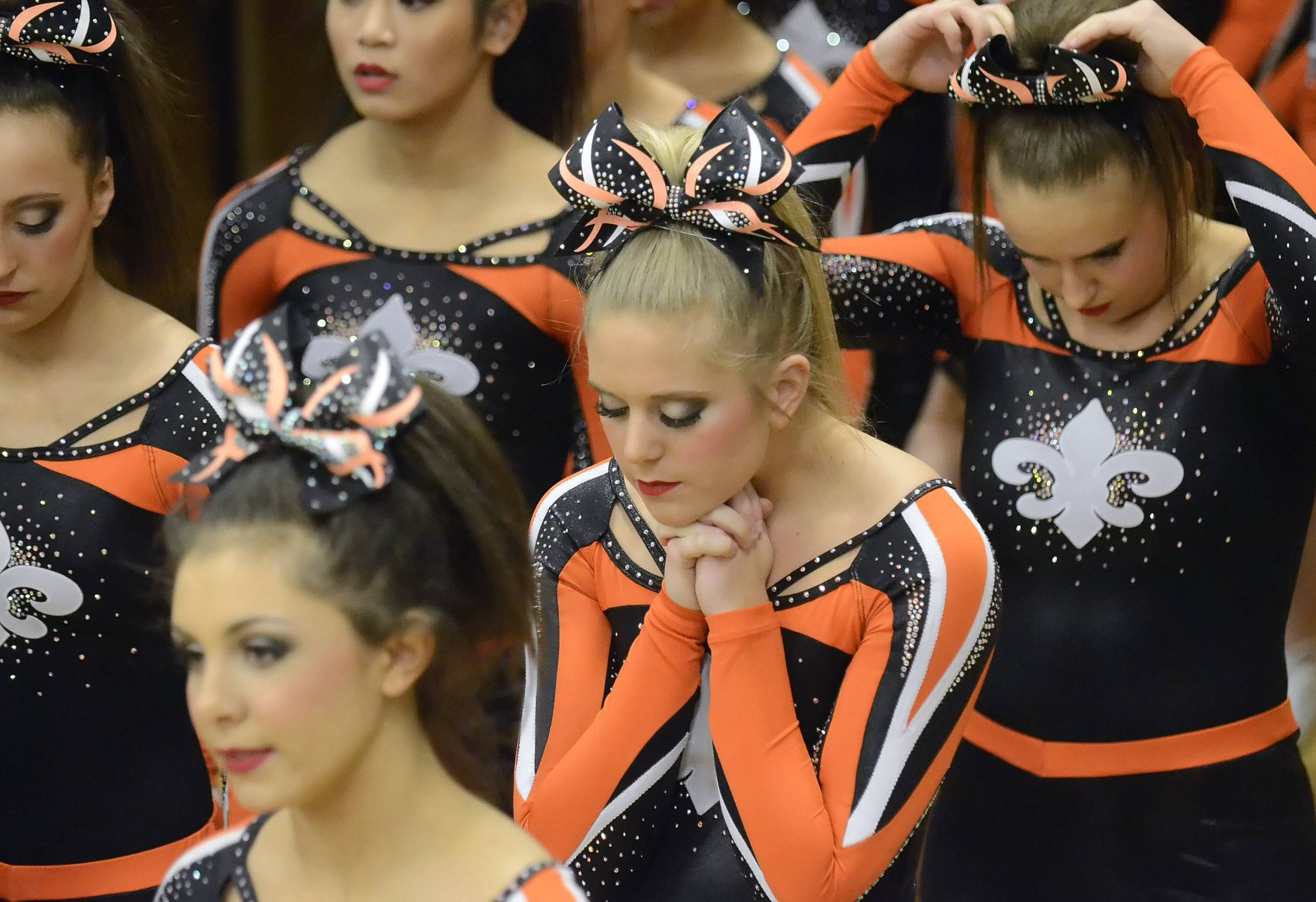 St. Charles East's Kennedy Gift, 15, takes a moment to herself before the Saints take the floor for their performance at the IHSA Cheerleading sectional at DeKalb High School Saturday.