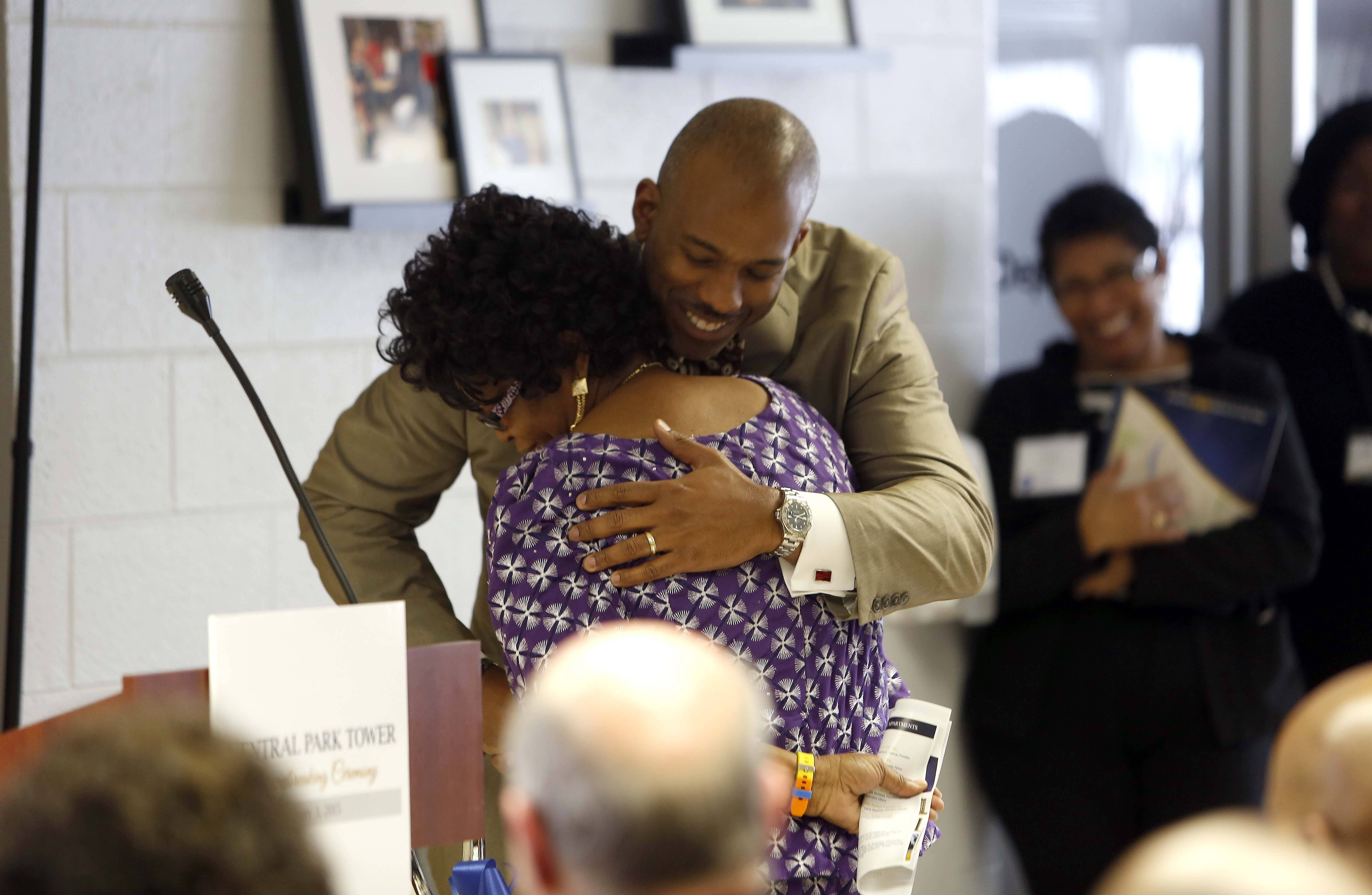 Central Park Tower resident Elizabeth Odumuyiwa gets a hug from Damon E. Duncan, CEO of the Housing Authority of Elgin, on Tuesday during the groundbreaking ceremony for a project to expand and renovate Central Park Tower at 120 S. State St.