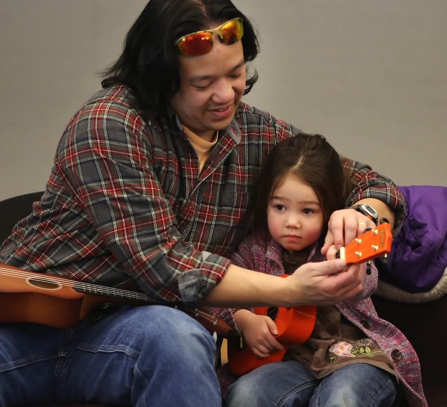 "Virgil Seribo of Buffalo Grove helps his daughter, Gigi, 4, with the ukulele during ""World Play Your 'Ukulele"" Day at the Vernon Area Public Library in Lincolnshire on Tuesday. Old Town School of Folk Music teacher Lanialoha Lee taught the class for children ages 3 to 5."