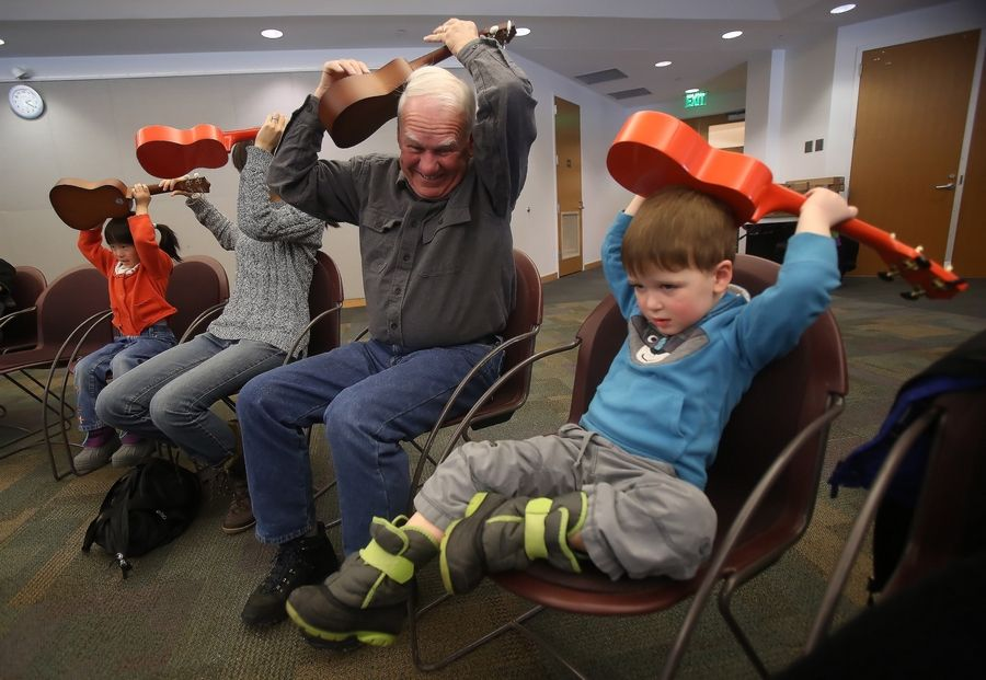 "Ethan Linn, 3, of Libertyville plays the ukulele with his grandfather, Mike McGrath, during ""World Play Your 'Ukulele"" Day at the Vernon Area Public Library in Lincolnshire on Tuesday. Old Town School of Folk Music teacher Lanialoha Lee taught the class for children ages 3 to 5."
